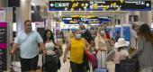 Travelers wearing protective face masks walking through Miami International Airport. (AP)