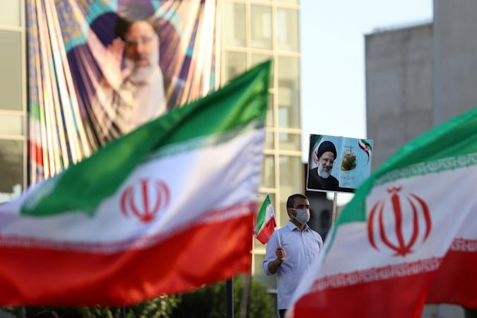 A supporter of presidential candidate Ebrahim Raisi holds a poster of him during an election rally in Tehran, Iran June 14, 2021. Majid Asgaripour/WANA (West Asia News Agency) via REUTERS ATTENTION EDITORS - THIS IMAGE HAS BEEN SUPPLIED BY A THIRD PARTY. ATTENTION EDITORS - THIS PICTURE WAS PROVIDED BY A THIRD PARTY