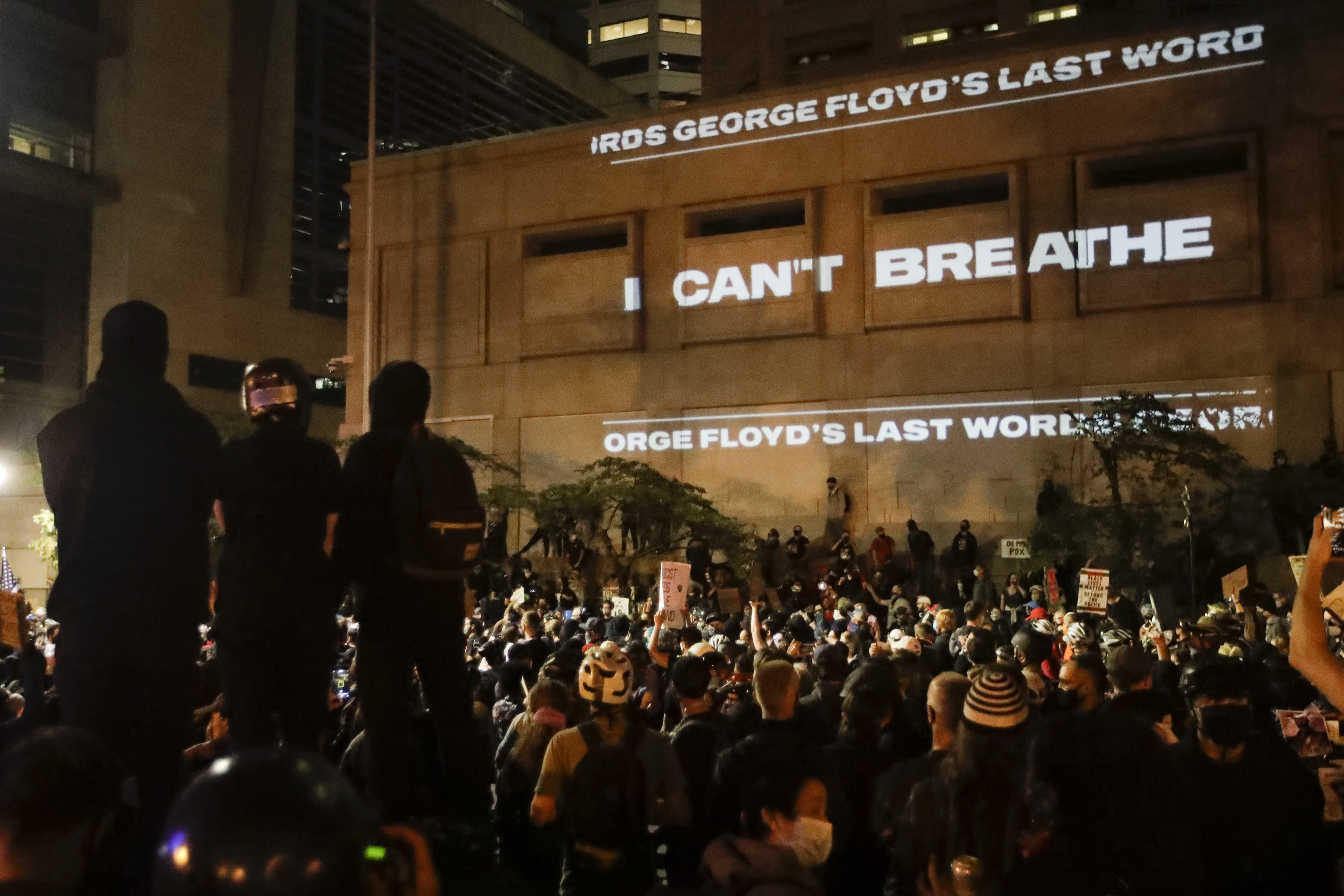 """FILE - In this Saturday, July 25, 2020, file photo, the words """"I can't breathe"""" are flashed on a wall during a Black Lives Matter protest in Portland, Ore. State legislatures across the U.S. are pushing an array of policing reforms after the demonstrations related to the death of George Floyd last spring, from banning chokeholds to making it easier to hold officers legally accountable for their actions. (AP Photo/Marcio Jose Sanchez, File)"""