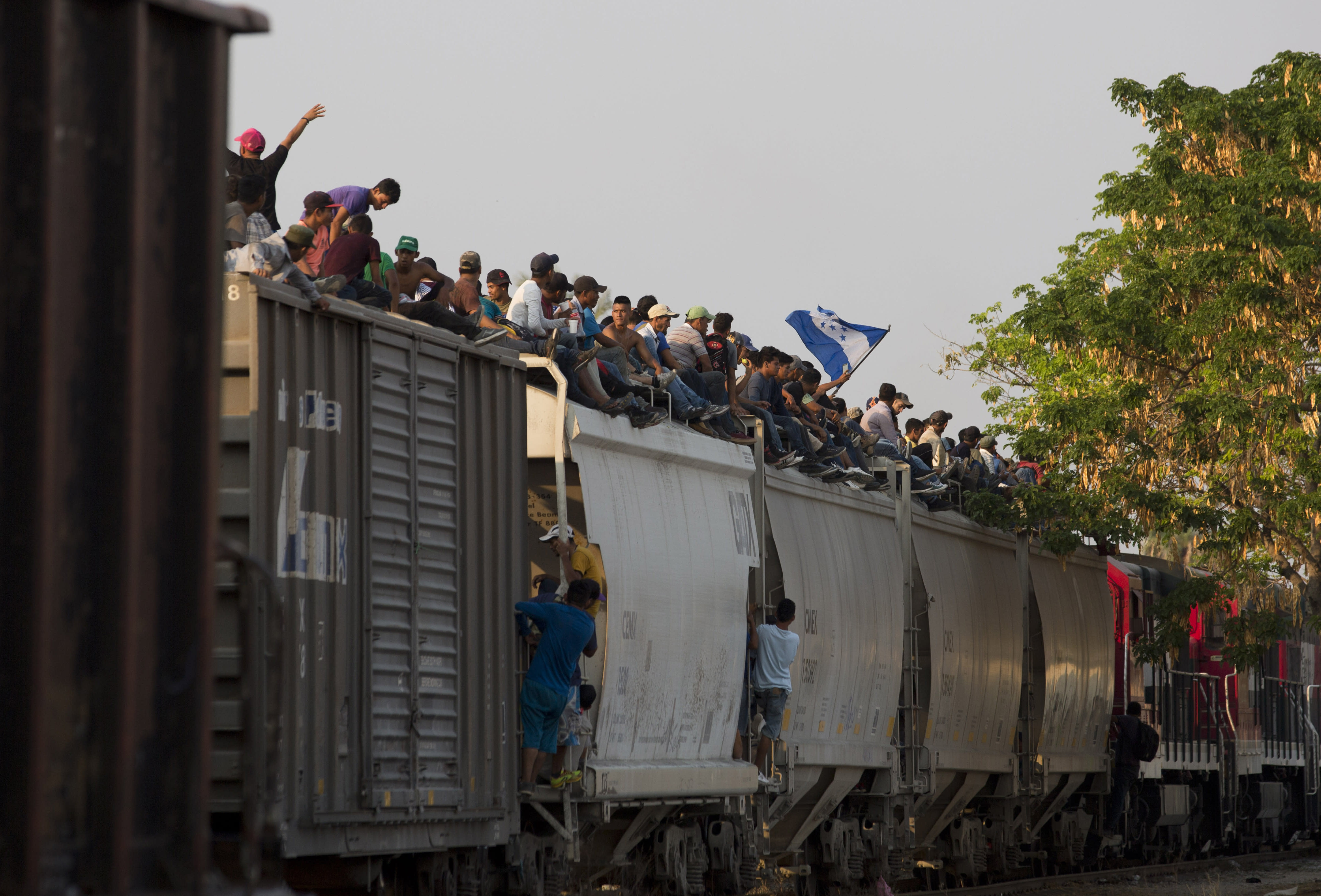 FILE - In this April 23, 2019 file photo, Central American migrants ride atop a freight train during their journey toward the U.S.-Mexico border, in Ixtepec, Oaxaca State, Mexico. Mexico said in Friday, Sept. 5, that it has complied with a 90-day deadline from the U.S. to reduce the flow of migrants through its territory, but activists say Mexico's crackdown has only forced migrants into greater desperation and more illicit, dangerous routes. (AP Photo/Moises Castillo, File)