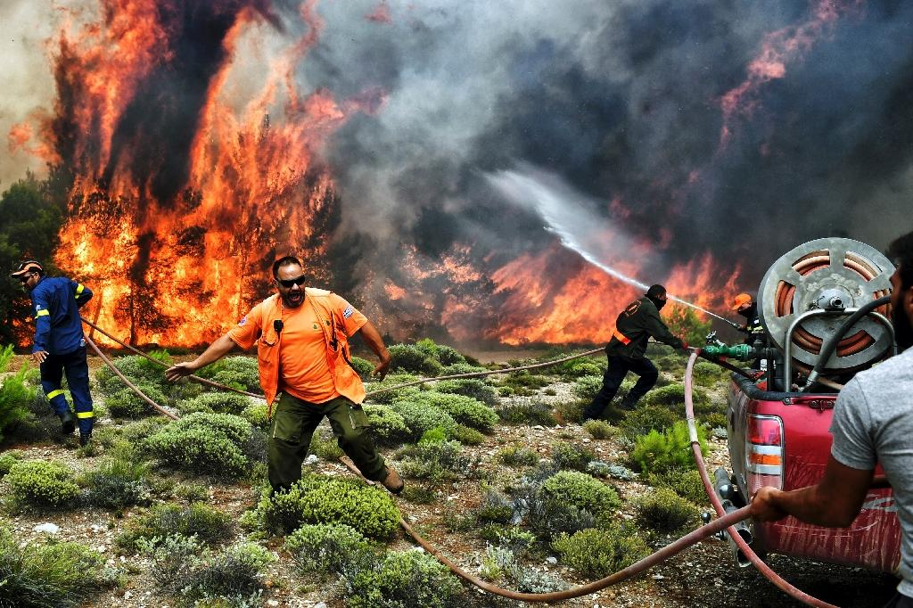 Firefighters and volunteers try to extinguish flames during a wildfire at the village of Kineta, near Athens, on July 24 (AFP Photo/Valerie GACHE)