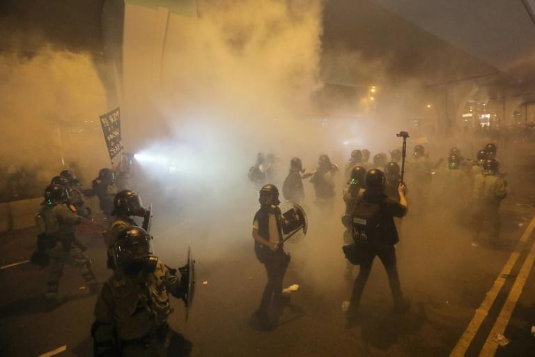 Riot police walk through tear gas during another weekend of unrest in Hong Kong that led to the arrest of dozens of pro-democracy protesters (AFP Photo/Vivek Prakash)