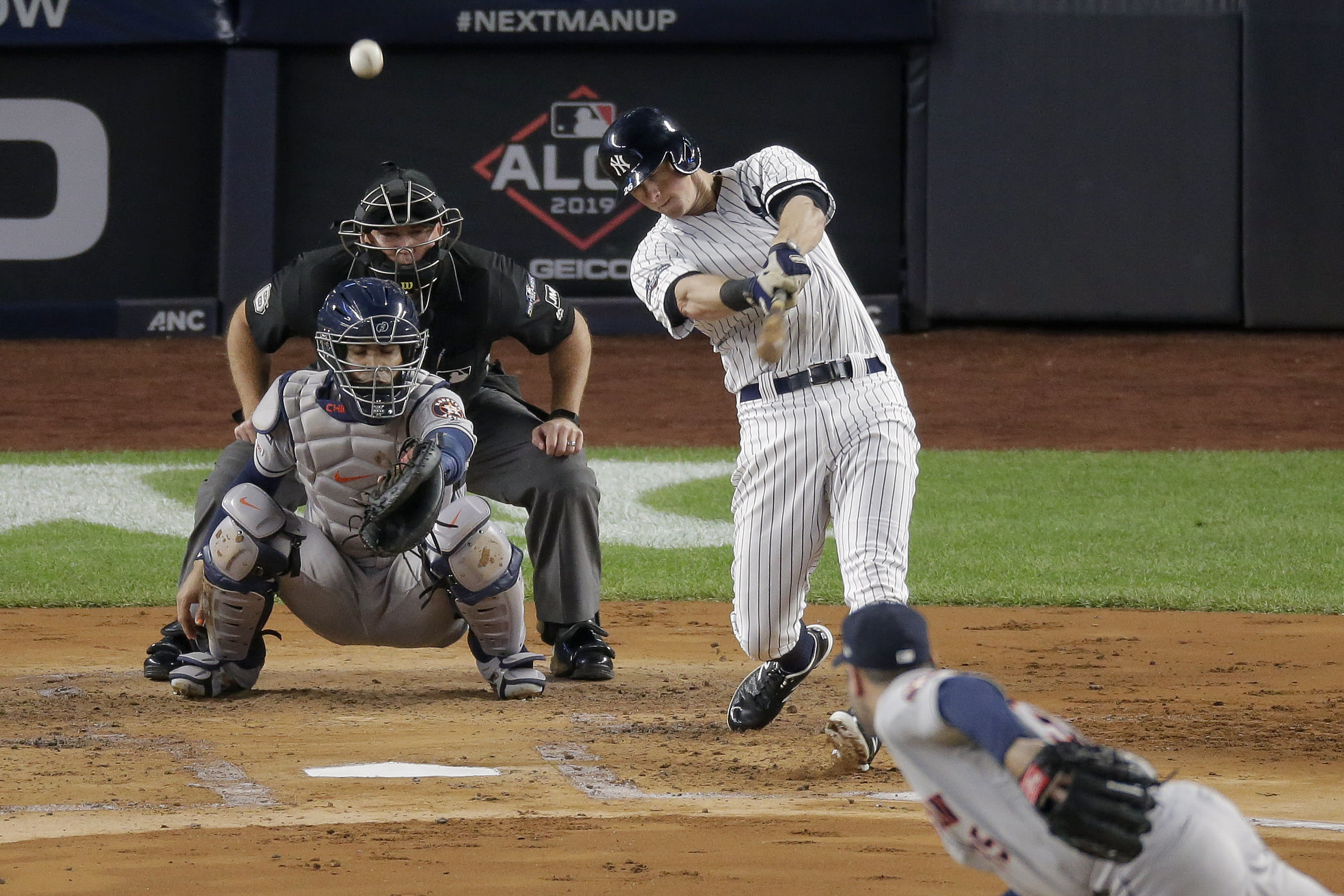FILE - In this Oct. 18, 2019, file photo, New York Yankees' DJ LeMahieu, top right, connects for a solo home run against the Houston Astros during the first inning of Game 5 of baseball's American League Championship Series in New York. LeMahieu returned to the field for the Yankees on Friday, July 17, 2020, after missing nearly two weeks with COVID-19. Manager Aaron Boone announced on July 4 that LeMahieu and right-hander Luis Cessa tested positive for the coronavirus before traveling to New York and said they were self-isolating at home. (AP Photo/Seth Wenig, File)