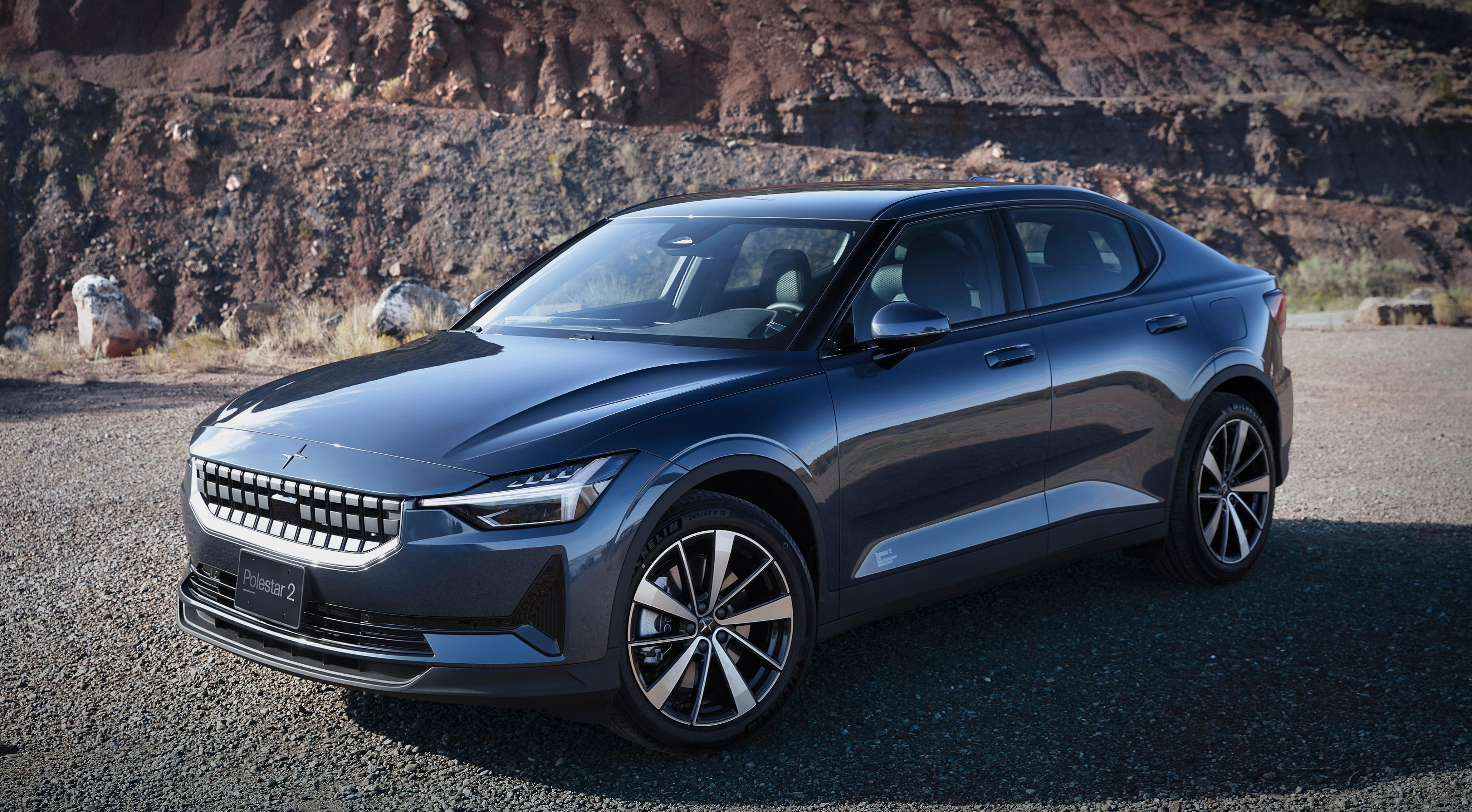 The Polestar 2 EV parked on a dirt and gravel road with a rocky cliff in the background.