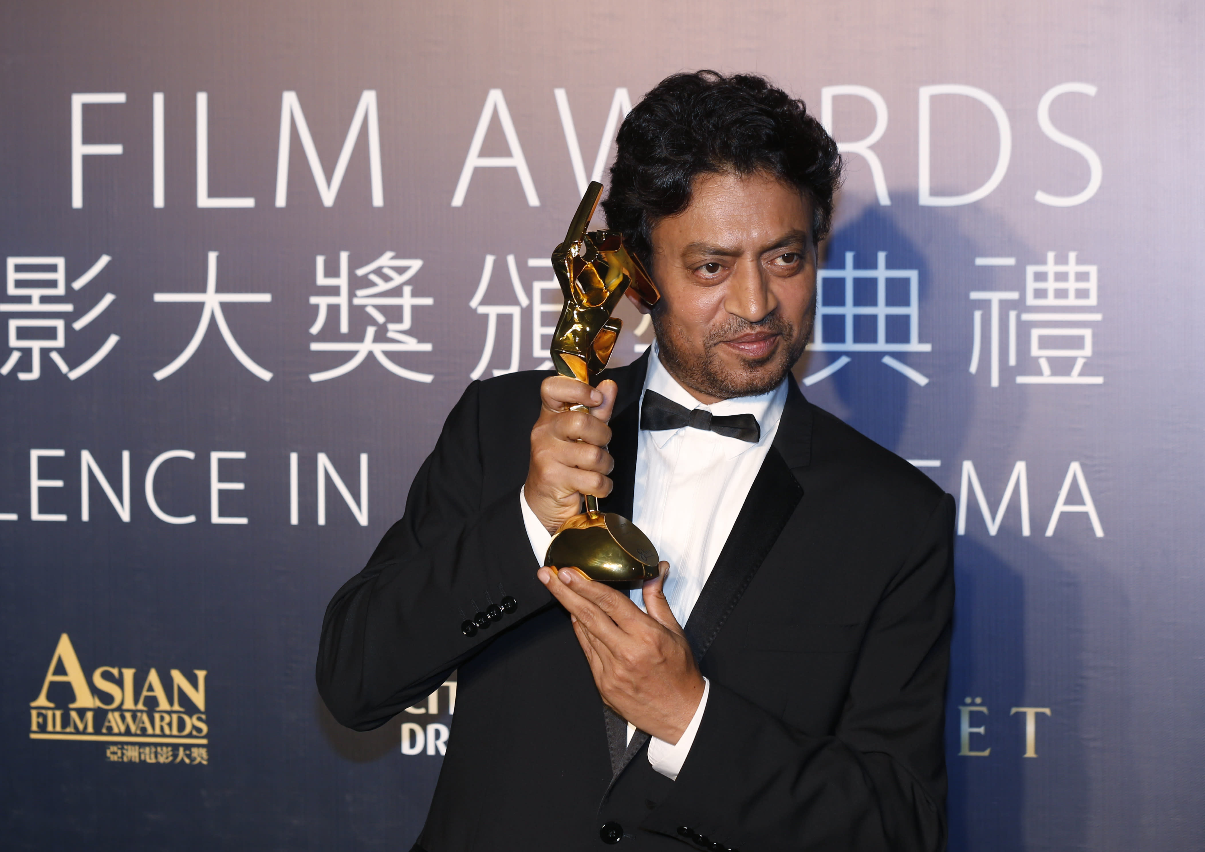 """Indian actor Irrfan Khan celebrates after winning the Best Actor for his movie """"The Lunchbox"""" of the Asian Film Awards in Macau Thursday, March 27, 2014. (AP Photo/Kin Cheung)"""