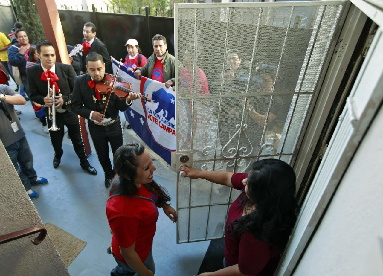 "Rosanna Del Rio, left, greets registered voter Edna Hernandez as the mariachi band ""Gallos de Jalisco"" serenades voters Tuesday, Nov. 6, 2012 in Los Angeles. (AP Photo/Damian Dovarganes)"