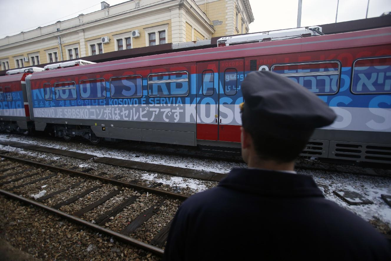 """A railroad worker stands by the first train decorated with letters that read """"Kosovo is Serbian"""" written in twenty languages departing from the Belgrade to Mitrovica, Kosovo at Belgrade's railway station, Serbia, Saturday, Jan. 14, 2017. Serbia has launched a railway link to Serb-dominated northern Kosovo despite protests from authorities in Pristina who described the move as a provocation and an aggressive violation of Kosovo's sovereignty. (AP Photo/Darko Vojinovic)"""