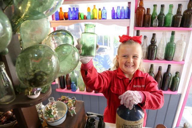 Seven-year-old schoolgirl raking in hundreds of pounds after opening antique bottle shop in her parents' back garden