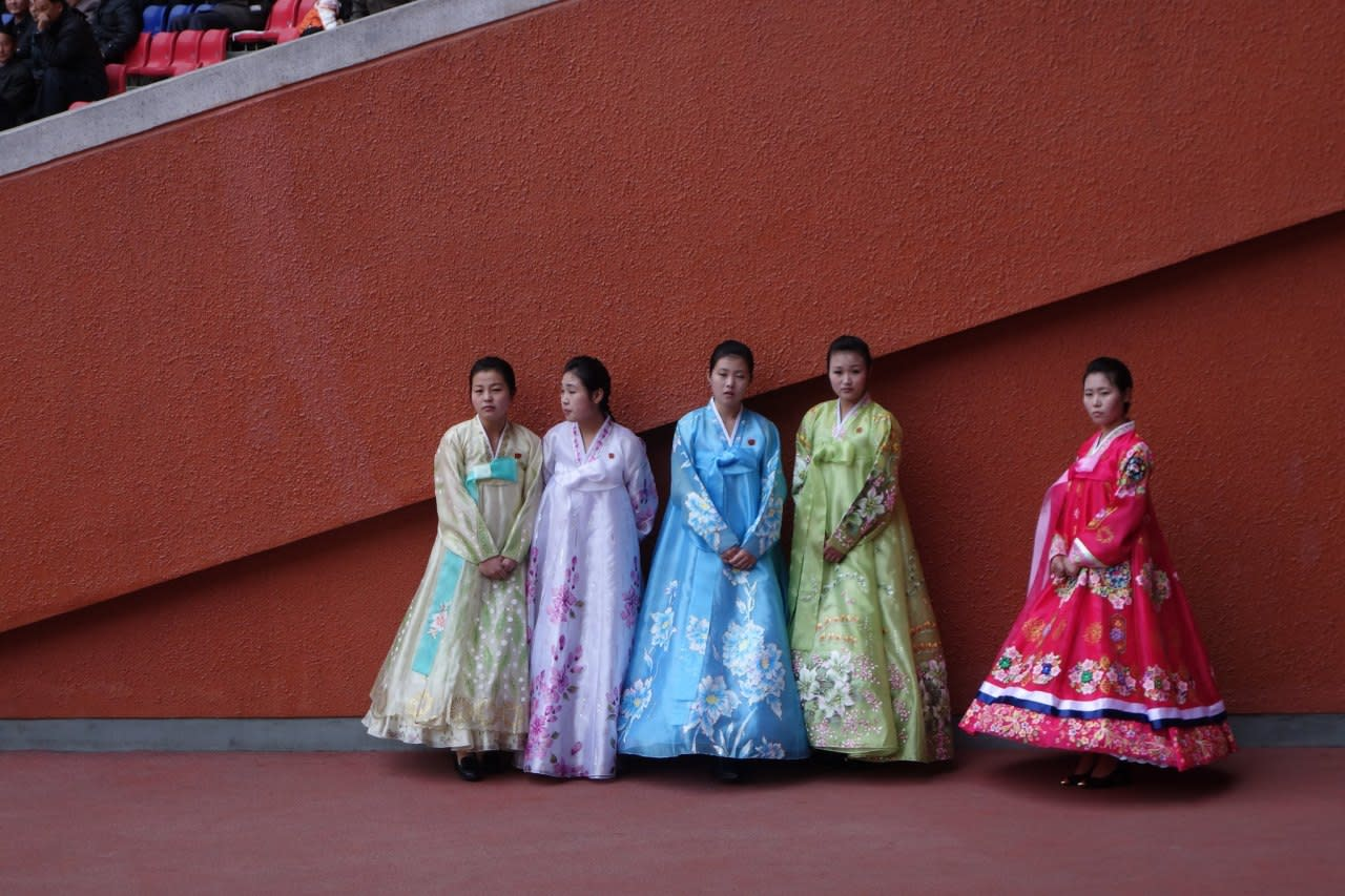 <p><i>Women stand hands together, dressed in their fine gowns of colour and decorative patterns. </i></p>