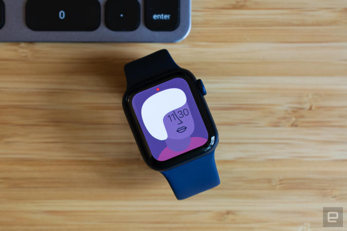 The Apple Watch Series 6 with an Artist watch face sitting on a wooden table.