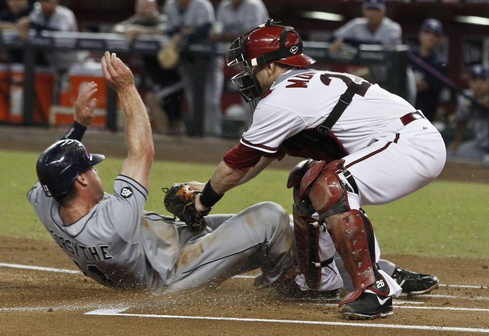 Logan Forsythe, izquierda, de los Padres de San Diego, anota una carrera deslizándose para evadir el guante del catcher Miguel Montero, de los Diamondbacks de Arizona, en el primer inning de un partido de la smayores el martes, 18 de septiembre del 2012.  (Foto AP/Ross D. Franklin)
