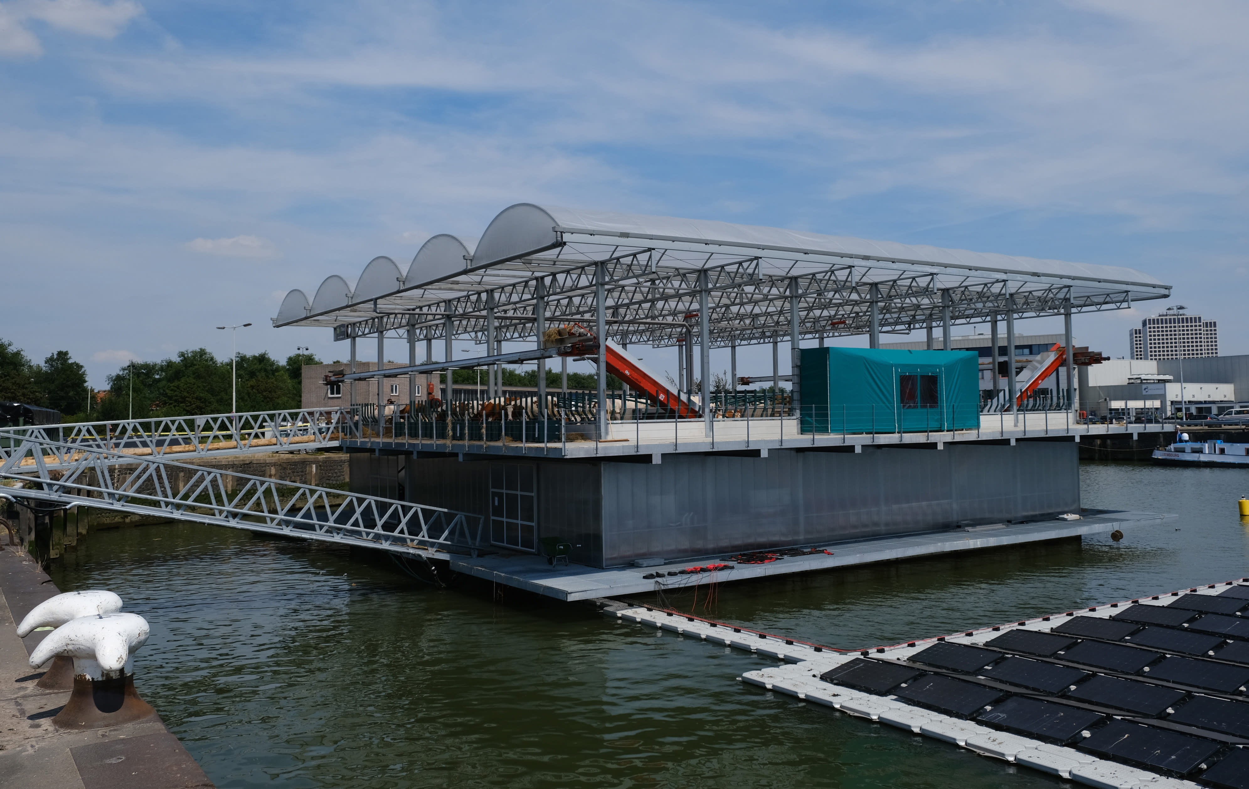 In this photo taken Monday, June 24, 2019, a futuristic three-storey floating farm is moored in Rotterdam harbour, Netherlands, where is is ideally placed to use waste products from a local golf course, brewing company, and a soccer club to claim its green credentials. The floating dairy farm has one robot that milks the cows, another that automatically scoops up the manure, and a roof designed to collect rain water, trailblazing a way to produce dairy foods within a busy modern city for growing populations, according to the small holding farmer Peter van Wingerden. (AP Photo/Mike Corder)