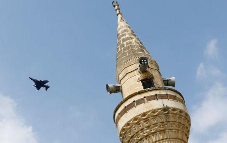 FILE PHOTO: A Turkish Air Force F-4 fighter jet flies over a minaret after it took off from Incirlik air base in Adana, Turkey, August 12, 2015. REUTERS/Murad Sezer/File Photo