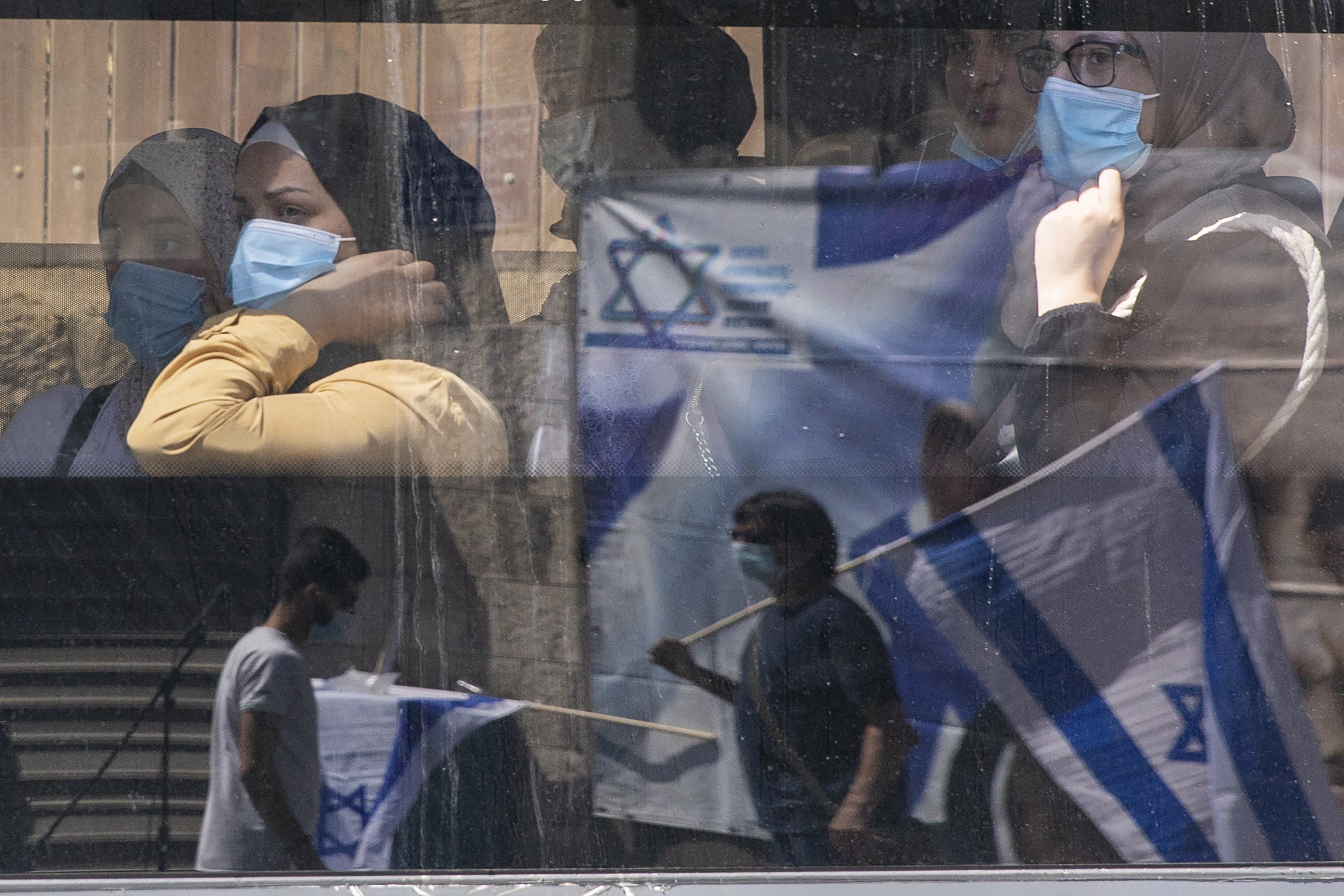 Women wearing face masks to protect from the coronavirus ride a public bus as they watch supporters of Prime Minister Benjamin Netanyahu wave flags outside the district court in Jerusalem, Sunday, July 19, 2020. The corruption trial of Netanyahu has resumed following a two-month hiatus. (AP Photo/Ariel Schalit)