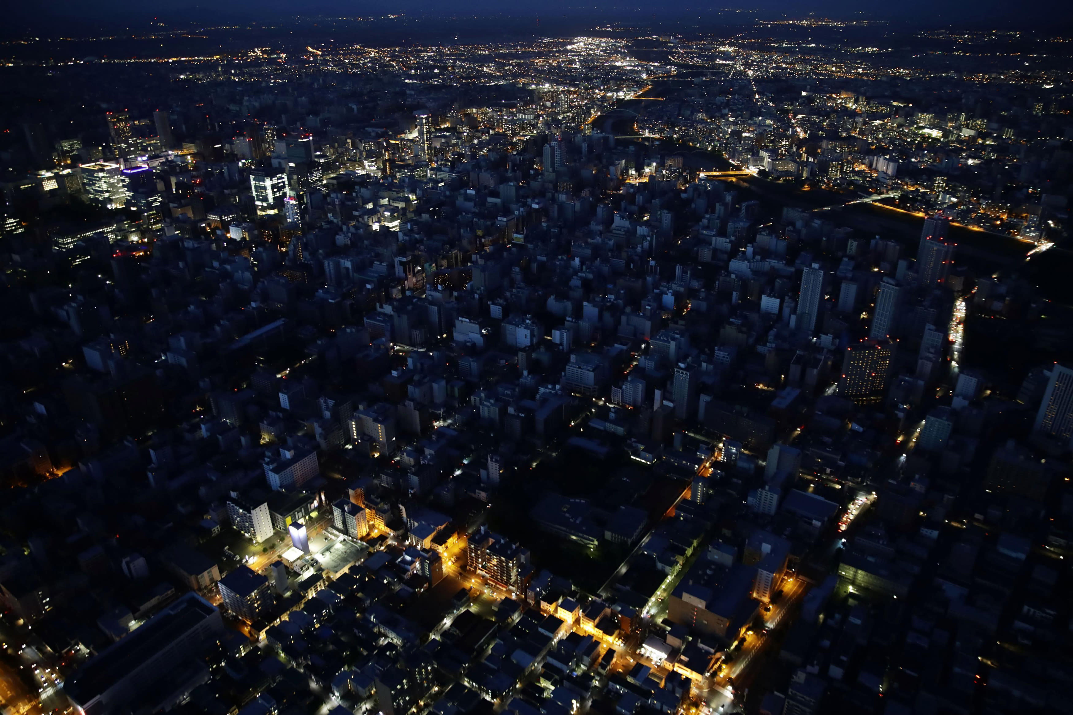 <p>Lights are off at central Sapporo, Hokkaido, northern Japan Thursday, Sept. 6, 2018. A powerful earthquake jolted Japan's northernmost main island of Hokkaido, buckling roads, knocking homes off their foundations and causing entire hillsides to collapse. (Photo: Hiroki Yamauchi/Kyodo News via AP) </p>