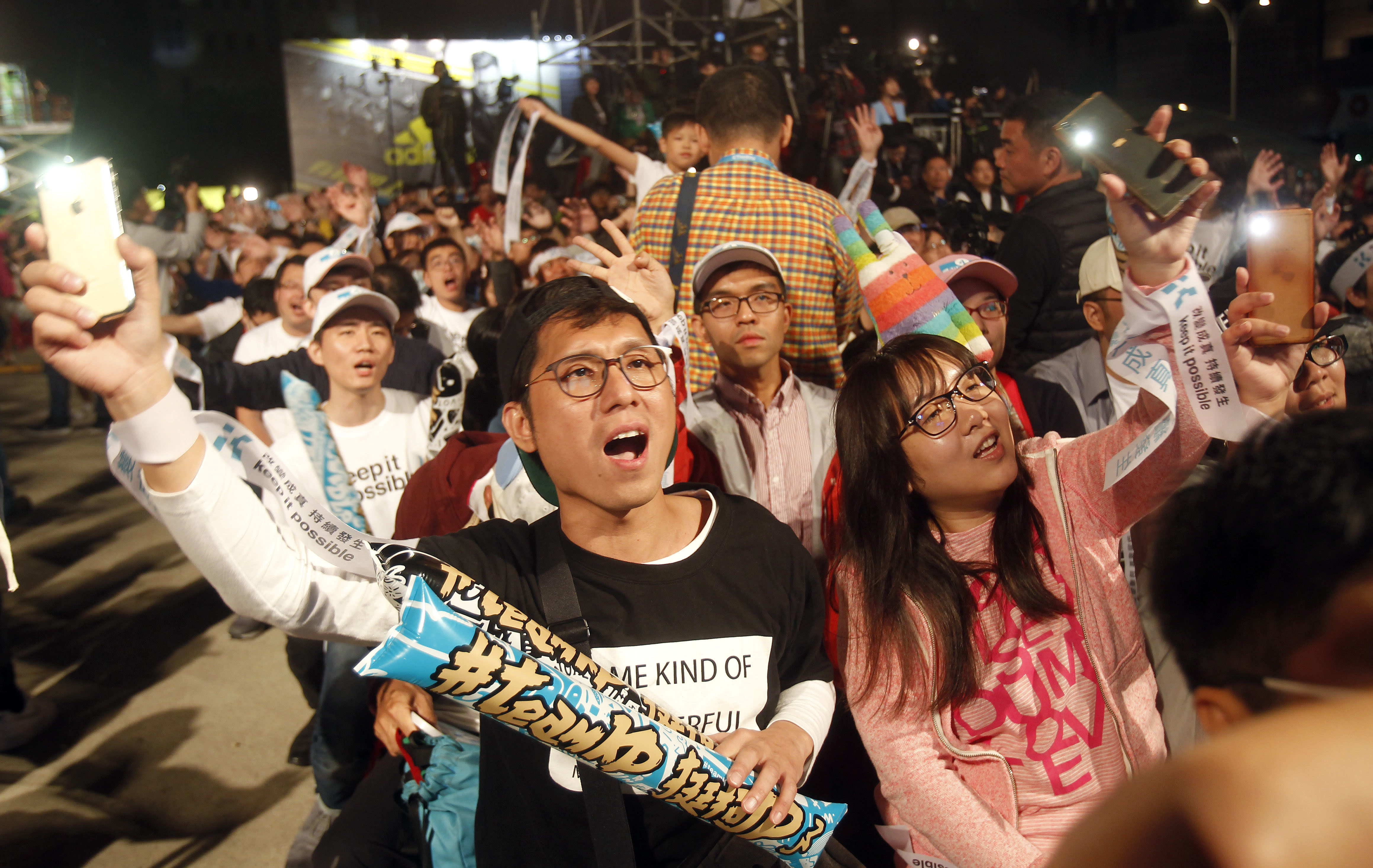Supporters of Taipei city mayor and city mayoral candidate Ko Wen-je cheer for Ko's victory in Taipei, Taiwan, Sunday early morning, Nov. 25, 2018. Taiwan's ruling party suffered a major defeat Saturday in local elections seen as a referendum on the administration of the island's independence-leaning president amid growing economic and political pressure from China. (AP Photo/Chiang Ying-ying)