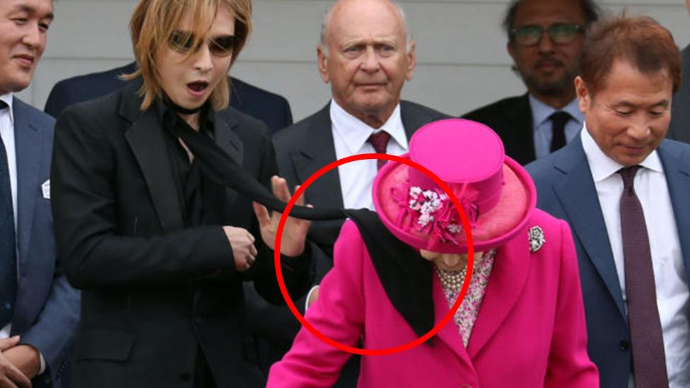 Man's horror as he hits Queen in the face with wayward scarf