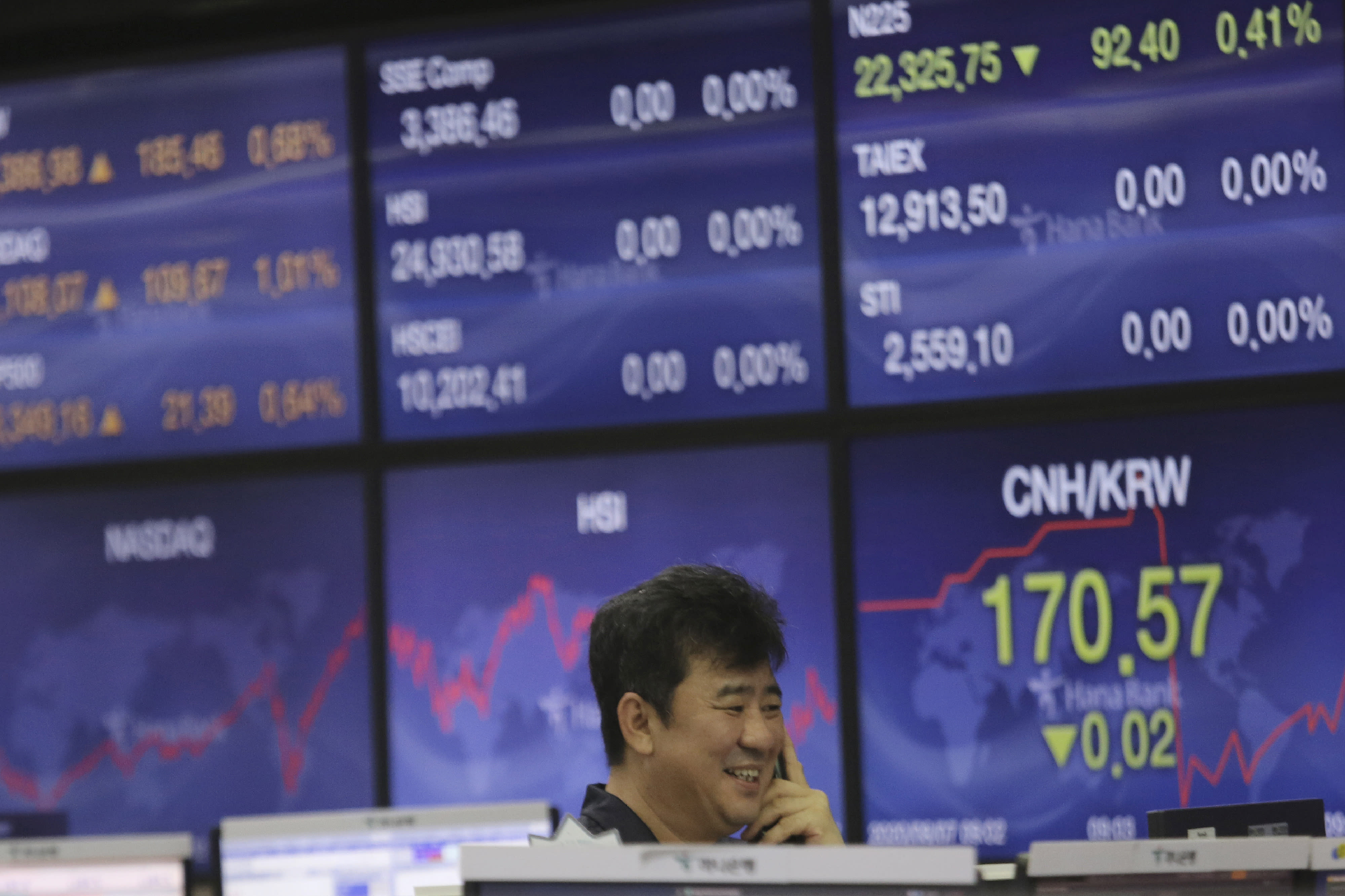 A currency trader smiles at the foreign exchange dealing room of the KEB Hana Bank headquarters in Seoul, South Korea, Friday, Aug. 7, 2020. Asian shares were mostly lower Friday in lackluster trading, as the region weighed continuing trade tensions over China and optimism about more fiscal stimulus for the ailing U.S. economy. (AP Photo/Ahn Young-joon)