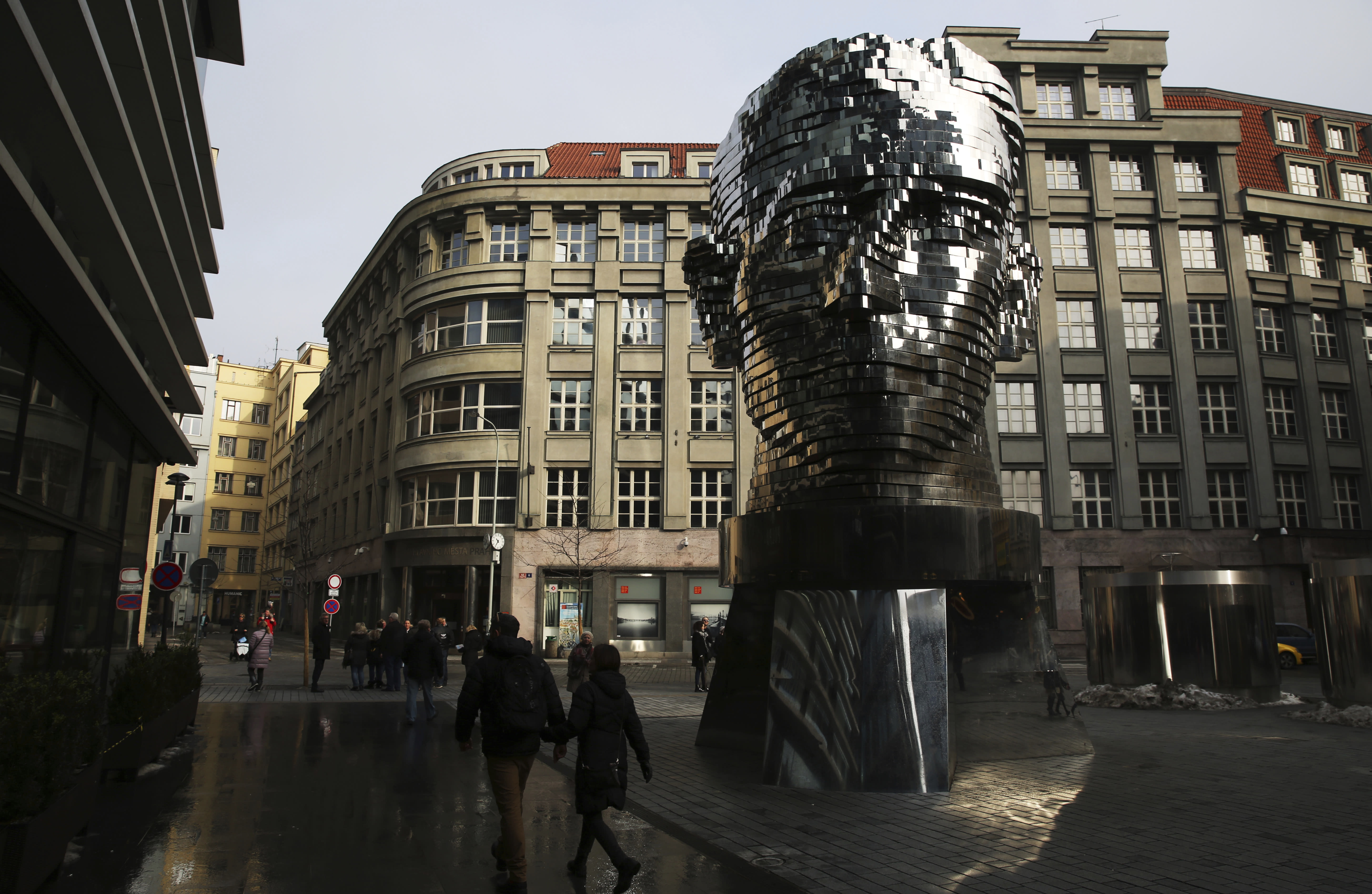 FILE - In this Feb. 4, 2017 file photo, tourists walk past a moving metal sculpture of writer Franz Kafka in his birth city of Prague, Czech Republic, on Saturday, Feb. 4, 2017. A long-hidden trove of unpublished works by Franz Kafka could soon be revealed following a decade-long battle over his literary estate that has drawn comparisons to some of his surreal tales. (AP Photo/Jon Gambrell, File)