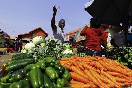 A vendor sprays his vegetables with water on a hot day to prevent the heat from damaging his wares ahead of Christmas sales in Abuja