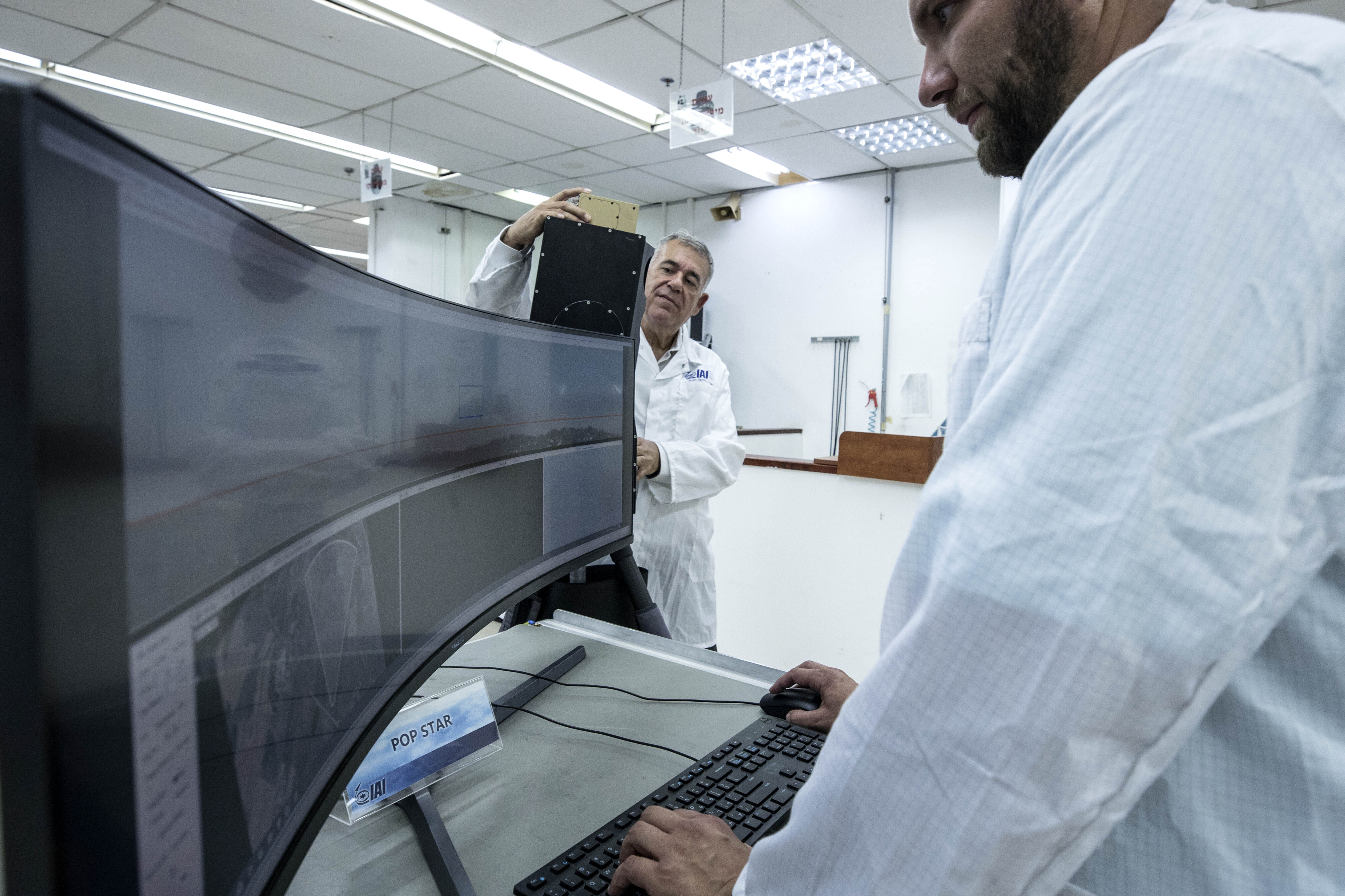 In this Monday, Sept. 9, 2019 photo, Ariel Gomez, right, and Boaz Leviy work on the Popstar system that can track and identify flying objects day or night without being detected, at Israel Aerospace Industries, in the Israeli town of Yehud near Tel Aviv. Israel has long been a dominant player in the military drone export business, developing small attack aircraft as well as long-range spy planes. Now, Israeli firms are at the forefront of a global industry developing means to protect against the drone threat. (AP Photo/Tsafrir Abayov)