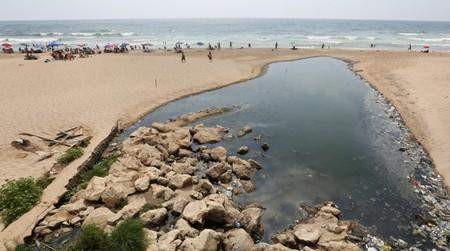 People swim at Ramlet al-Bayda public beach near a sewage outlet in Beirut