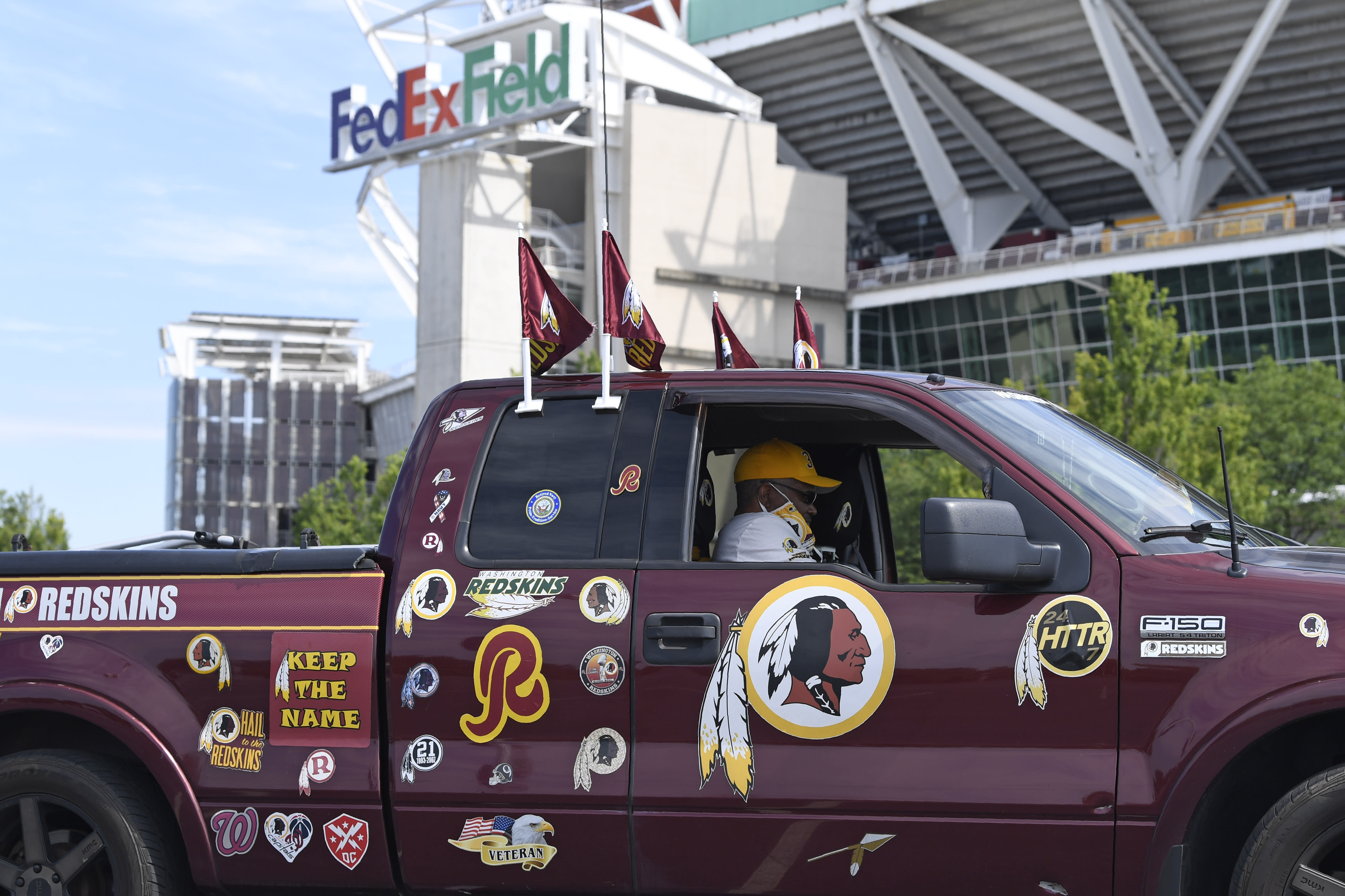 """Rodney Johnson of Chesapeake, Va., sits in his truck outside FedEx Field in Landover, Md., Monday, July 13, 2020. The Washington NFL franchise announced Monday that it will drop the """"Redskins"""" name and Indian head logo immediately, bowing to decades of criticism that they are offensive to Native Americans. (AP Photo/Susan Walsh)"""