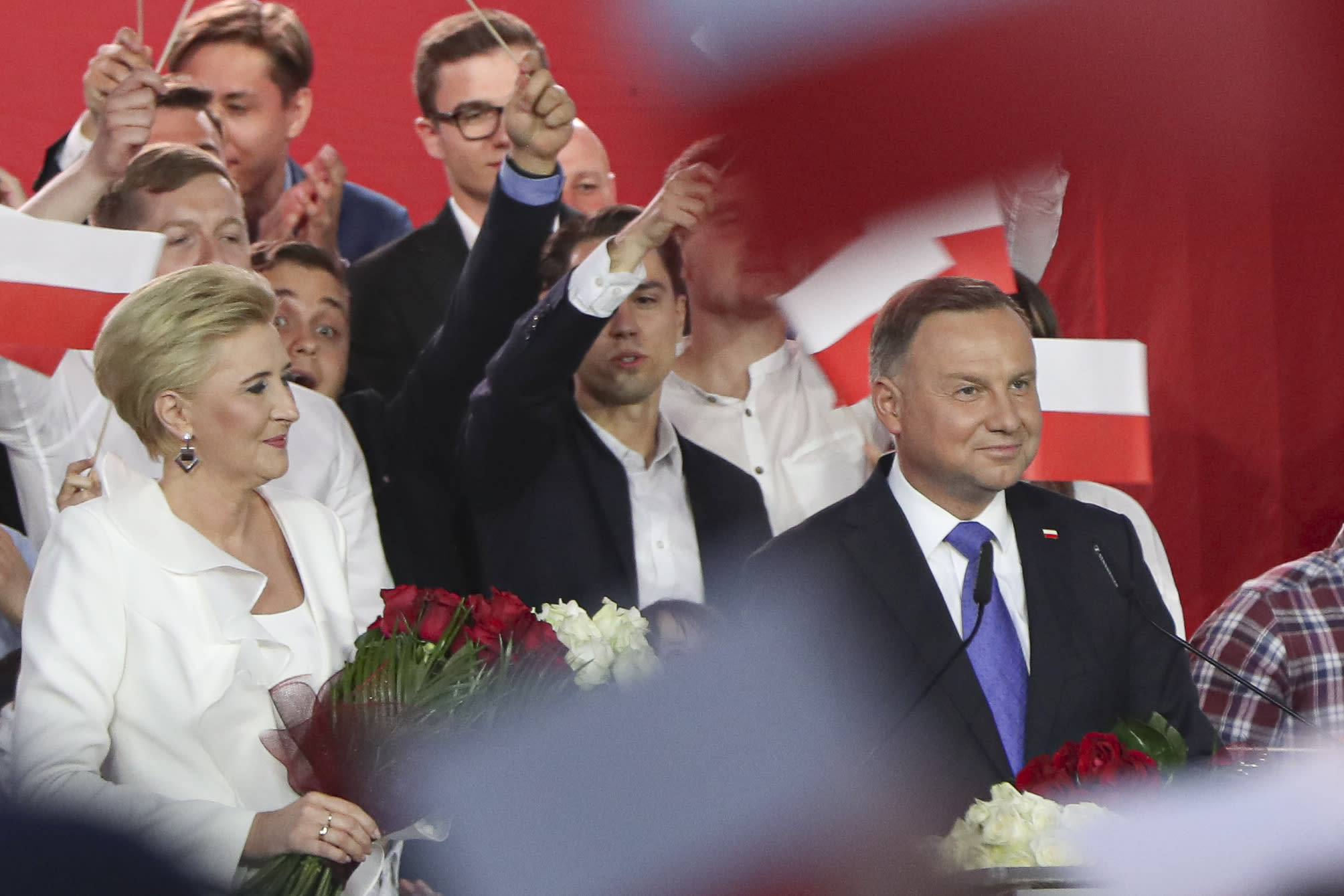 Incumbent President Andrzej Duda, right, smiles next to his wife Agata Kornhauser-Duda while addressing supporters in Pultusk, Poland, Sunday, July 12, 2020. Conservative Duda ran against liberal Warsaw Mayor Rafal Trzaskowski in a razor-blade-close presidential election runoff and exit poll shows election is too close to call. (AP Photo/Czarek Sokolowski)