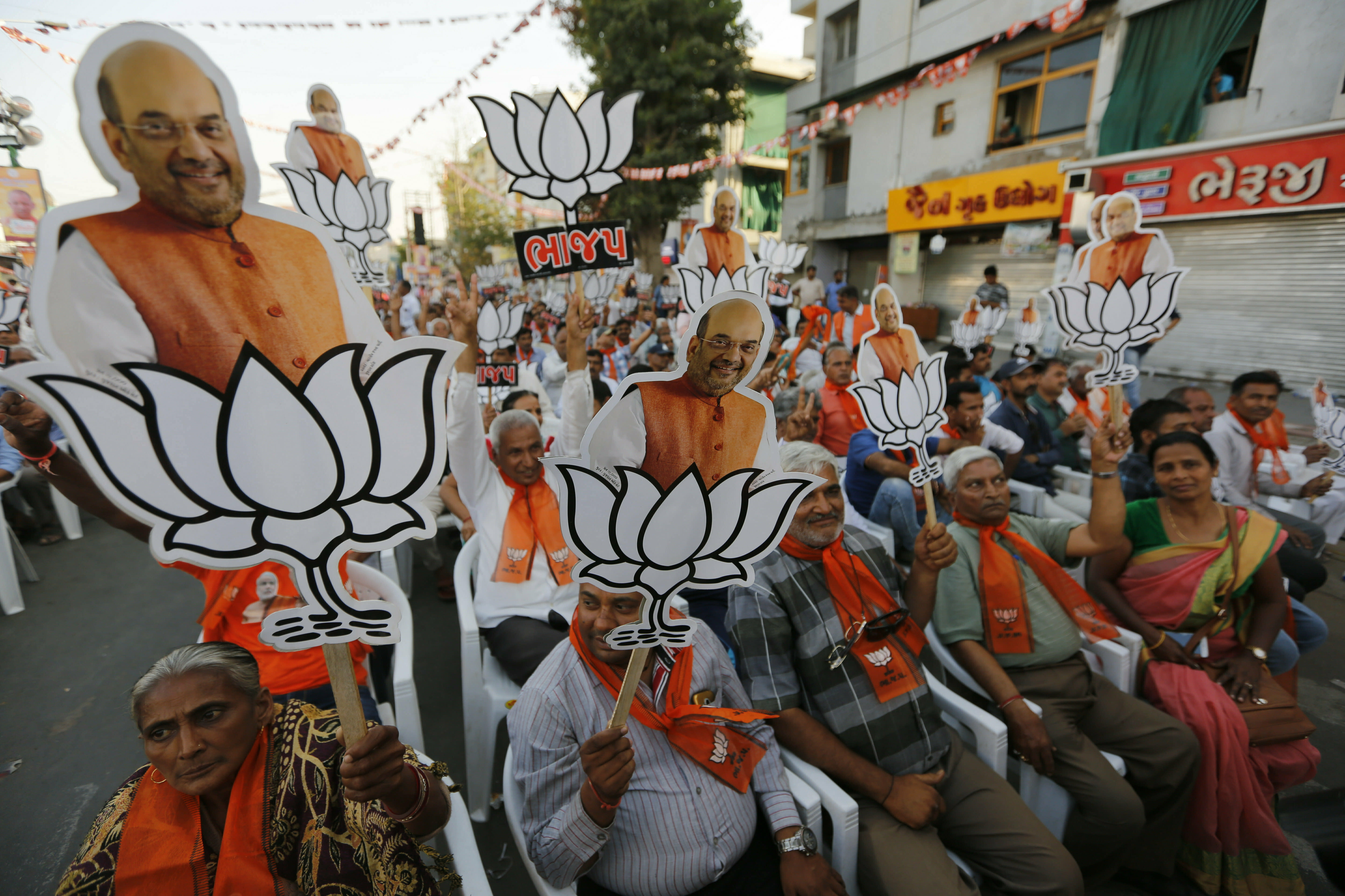 Supporters of India's ruling Bharatiya Janata Party (BJP) hold cutouts of party president Amit Shah with the party symbol during a public rally in Ahmadabad, India, Tuesday, March 26, 2019. India's national election will be held in seven phases between April 11 and May 19. (AP Photo/Ajit Solanki)