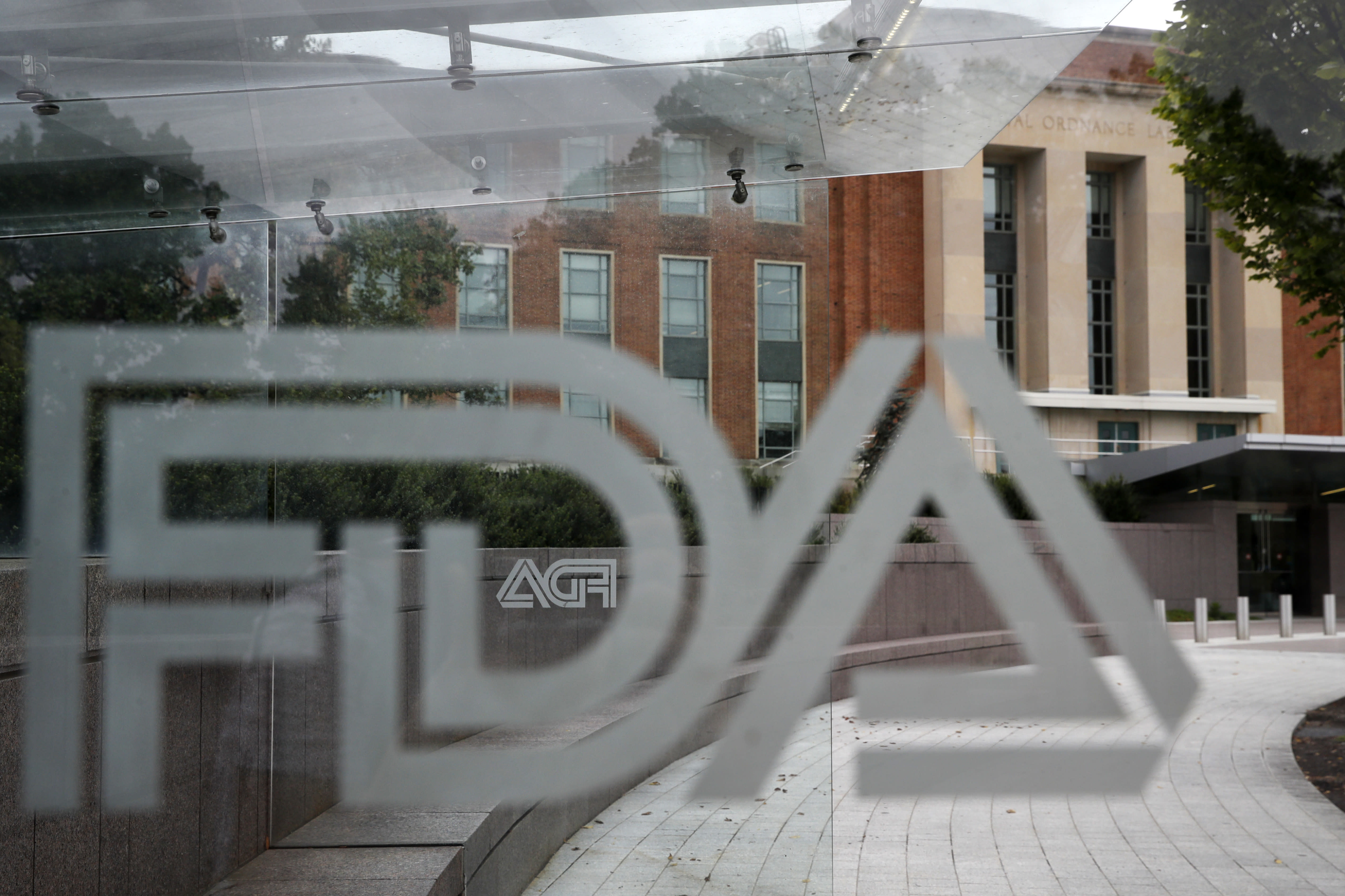 """FILE - This Aug. 2, 2018, file photo shows the U.S. Food and Drug Administration building behind FDA logos at a bus stop on the agency's campus in Silver Spring, Md. In a report to Congress and an accompanying """"playbook"""" for states and localities, key federal health agencies and the Defense Department sketched out complex plans for a vaccination campaign to begin gradually early next year or later in 2020, eventually ramping up to reach any American who wants a shot. The Pentagon is involved with the distribution of vaccines, but civilian health workers will be the ones giving shots. (AP Photo/Jacquelyn Martin, File)"""