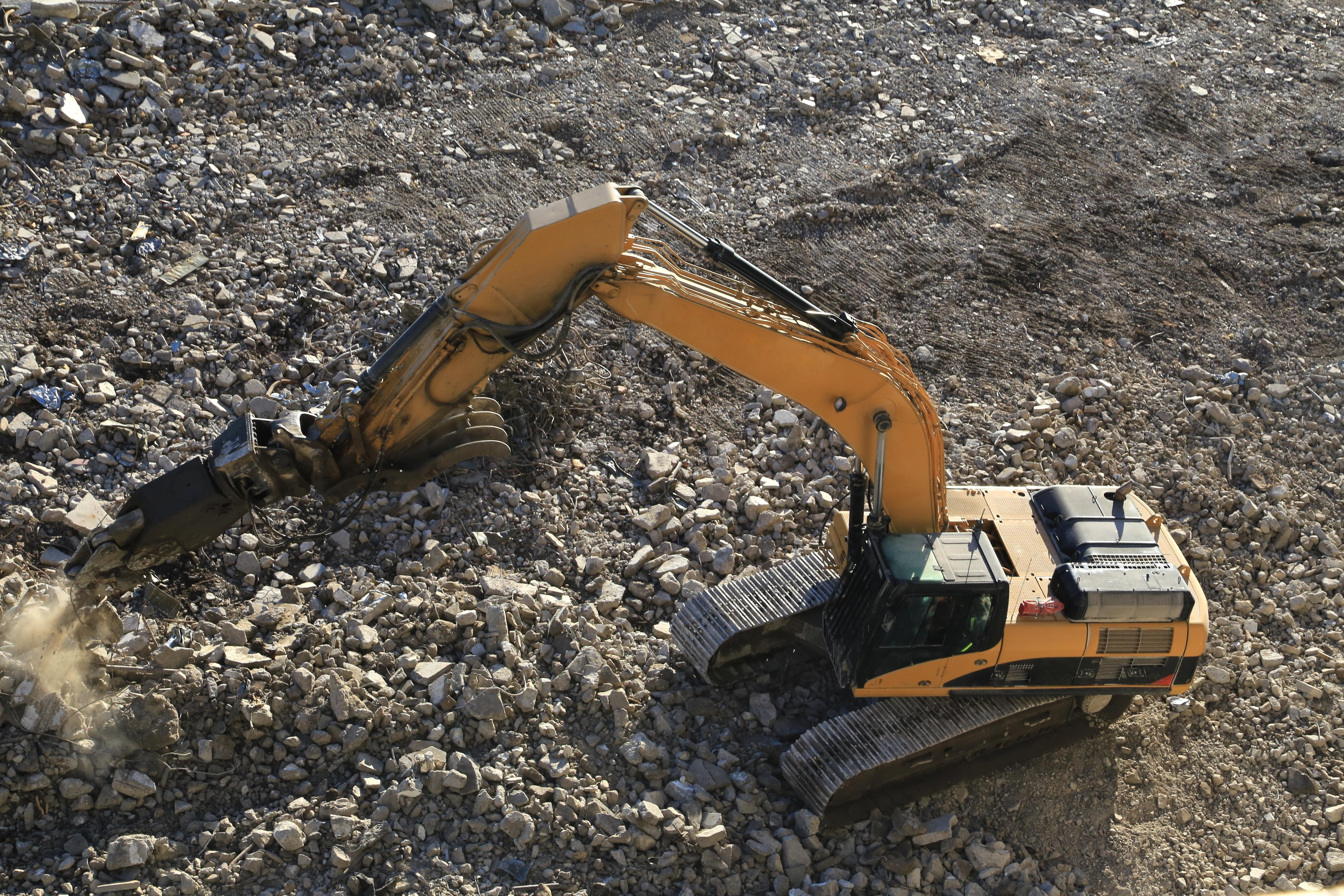 Tracked excavator uses a jack hammer to breakup concrete