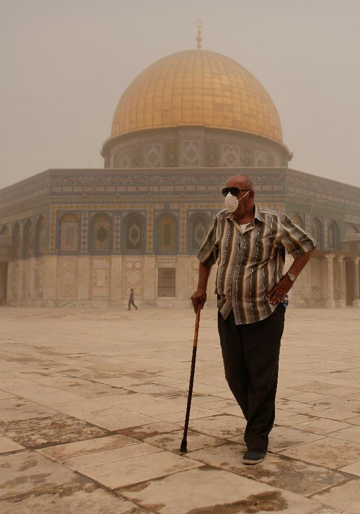 A Palestinian man wears a mask to protect himself from dust as he walks past the Dome of the Rock mosque in the al-Aqsa Mosque compound, in the old city of Jerusalem, during a sandstorm on September 8, 2015 (AFP Photo/Ahmad Gharabli)