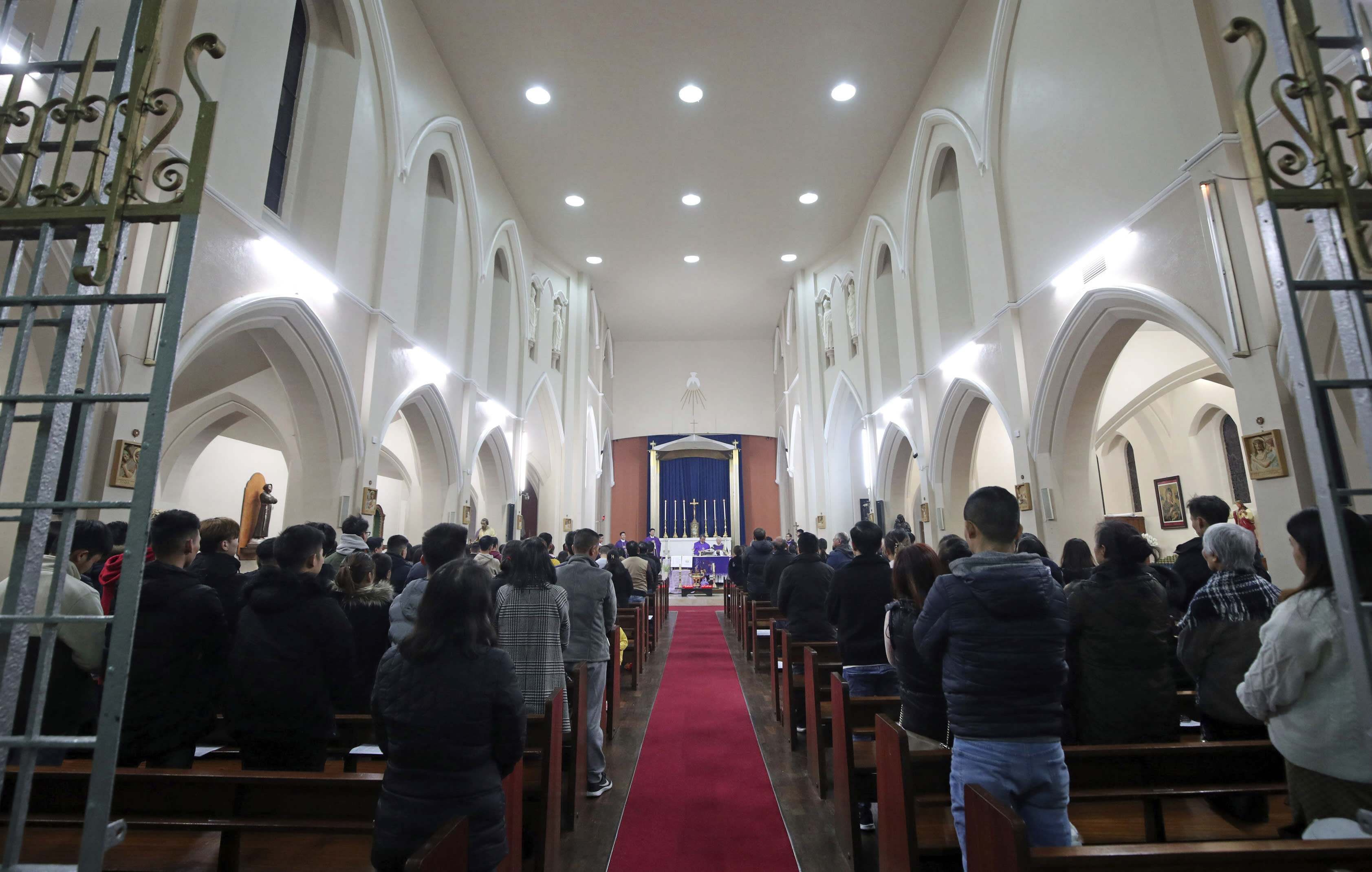 The priest of the Vietnamese Catholic Cathedral in east London, Father Simon Thang Duc Nguyen, speaks at The Holy Name and Our Lady of the Sacred Heart Church, London's Vietnamese church, in east London. Saturday Nov. 2, 2019, during a service and vigil to honor the 39 victims who died in a refrigerated truck container found on Oct. 23. The community is mourning the unidentified victims, who were trying to enter Britain in hopes of finding opportunity. (Yui Mok/PA via AP)