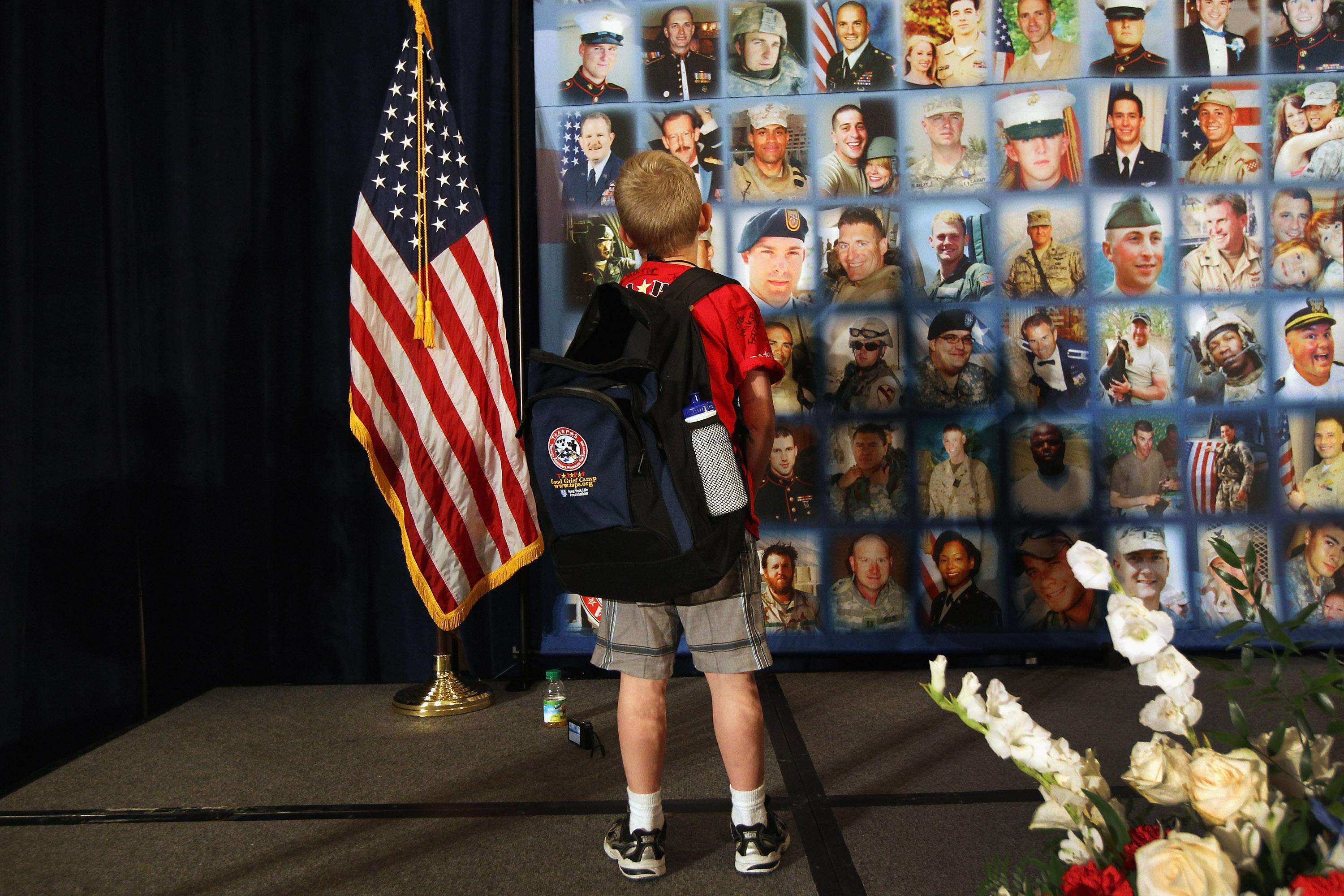 """A child looks over portraits of fallen military personel while participating in the TAPS """"Good Grief Camp"""" on May 27, 2012 in Washington, DC. Five hundred military children and teens, many of whom had a parent that was killed in the Afghan and Iraq wars, attended the annual four-day """"Good Grief Camp"""" in Arlington, VA and Washington, DC, which is run by TAPS (Tragedy Assistance Program for Survivors). The camp helped them learn coping skills and build relationships so they know they are not alone in the grief of their loved one. They met others of their own age group, learned together and shared their feelings, both through group activities and one-on-one mentors, who are all active duty or former military servicemembers. Some 1,200 adults, most of whom are grieving parents and spouses, also attend the National Military Survival Seminar held concurrently with the children's camp. The TAPS slogan is """"Remember the Love. Celebrate the Life. Share the Journey."""" (Photo by John Moore/Getty Images)"""
