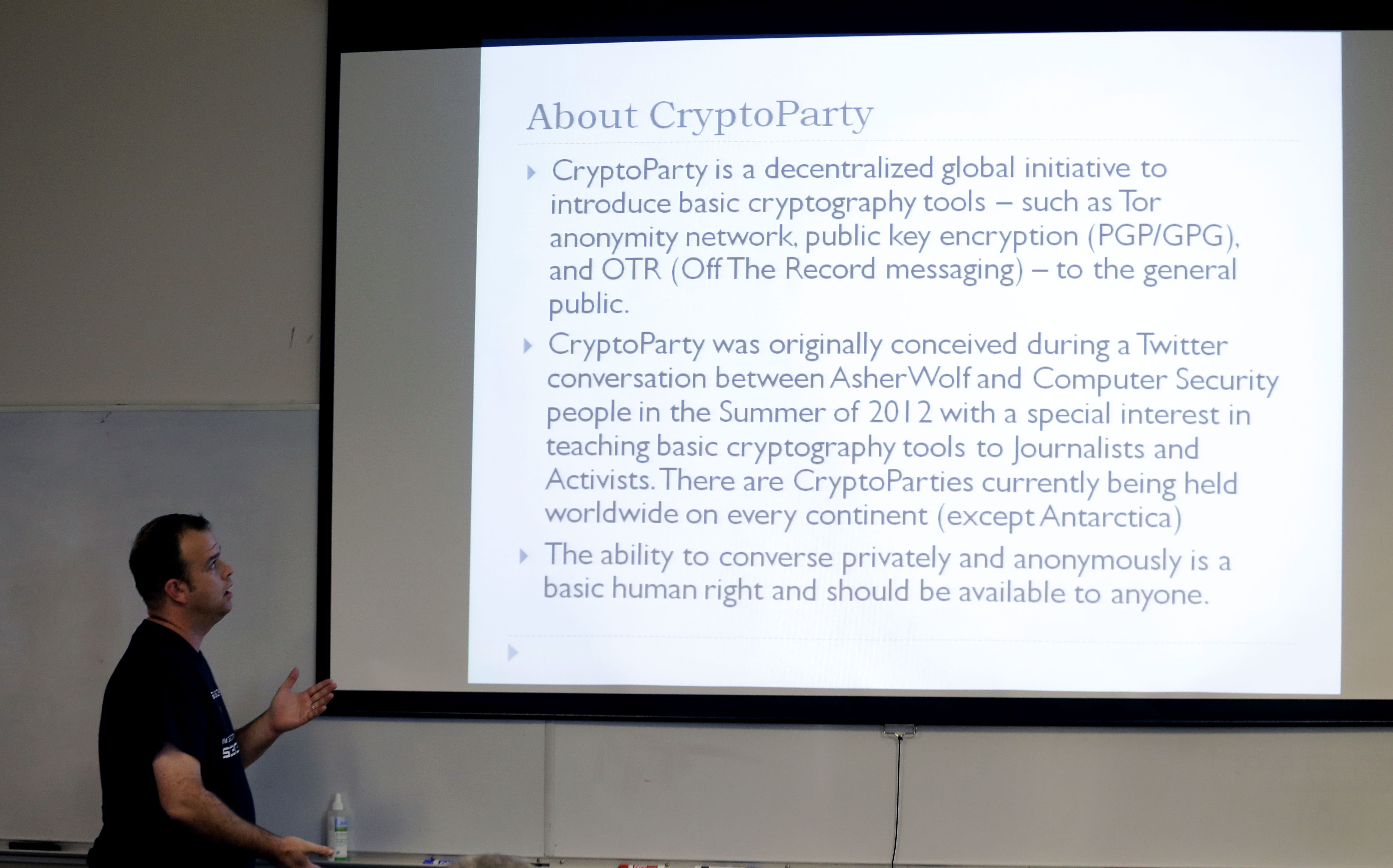 "In this Thursday, July 18, 2013, photo, information technology professional Josh Scott looks up at a visual he uses while hosting a monthly ""Cryptoparty"" in Dallas. Across the Internet, users are talking about changes small and large, from using more encryption and stronger passwords to much more extreme measures such as ditching cellphones and using cash over credit cards. The conversations play out daily on Reddit, Twitter and other networks, and have spread to offline life with so-called ""Cryptoparty"" gatherings in cities including Dallas, Atlanta and Oakland, Calif. (AP Photo/LM Otero)"