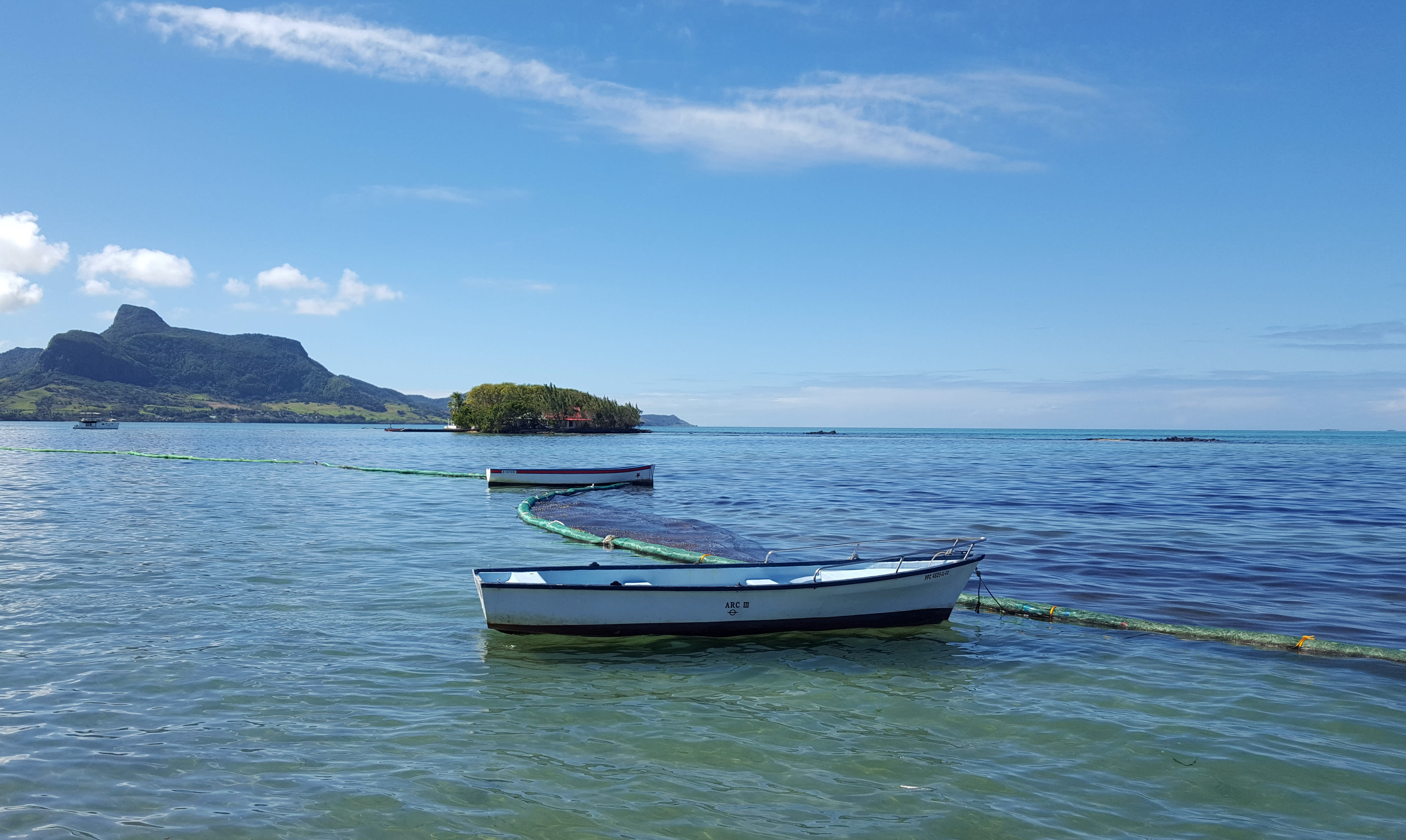 This photo taken and provided by Sophie Seneque, shows a boom, a temporary floating barrier used to contain the oil spill in Mahebourg Waterfront, Mauritius, Saturday Aug. 8, 2020, after it leaked from the MV Wakashio, a bulk carrier ship that recently ran aground off the southeast coast of Mauritius. Thousands of students, environmental activists and residents of Mauritius are working around the clock to reduce the damage done to the Indian Ocean island from an oil spill after a ship ran aground on a coral reef. Shipping officials said an estimated 1 ton of oil from the Japanese ship's cargo of 4 tons has escaped into the sea. Workers were trying to stop more oil from leaking, but with high winds and rough seas on Sunday there were reports of new cracks in the ship's hull. (Sophie Seneque via AP)
