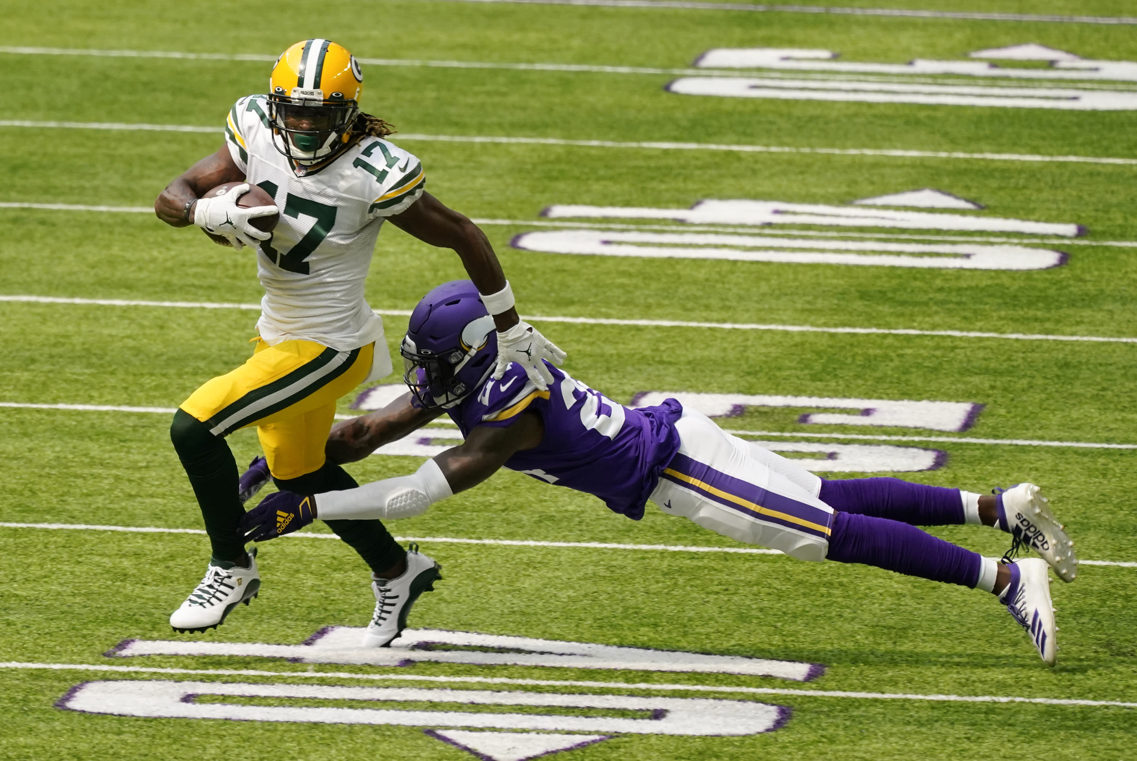 Green Bay Packers wide receiver Davante Adams breaks a tackle by Minnesota Vikings defensive back Holton Hill (24) during the first half of an NFL football game, Sunday, Sept. 13, 2020, in Minneapolis. (AP Photo/Jim Mone)