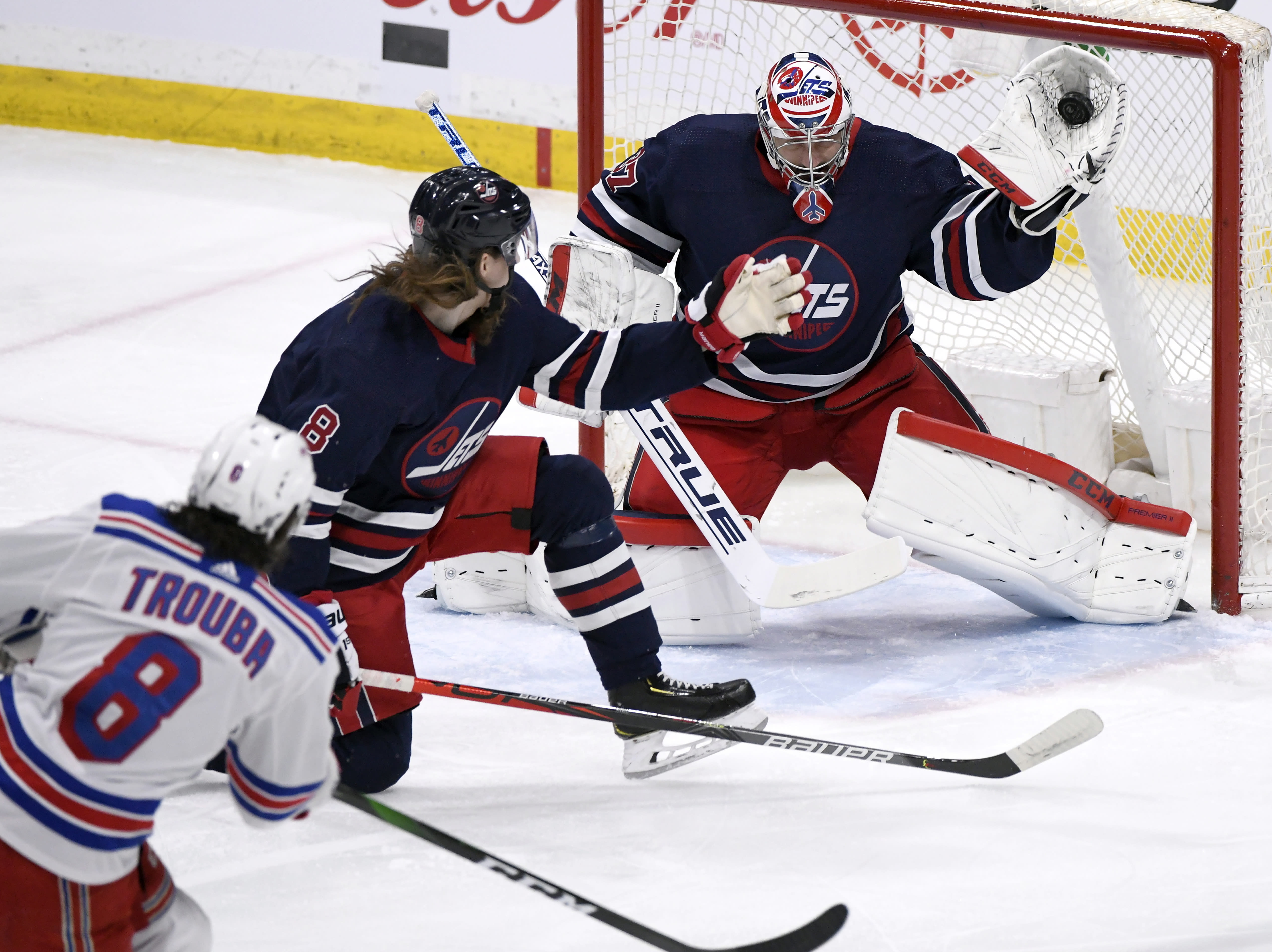 FILE - In this Feb. 11, 2020, file photo, Winnipeg Jets goaltender Connor Hellebuyck (37) makes a save on a shot from New York Rangers' Jacob Trouba (8) during first-period NHL hockey game action in Winnipeg, Manitoba. Hellebuyck has won the Vezina Trophy as top goaltender. (Fred Greenslade/The Canadian Press via AP, File)