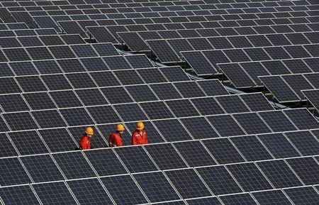 Workers walk among newly installed solar panels at a plant in Zhouquan township of Tongxiang