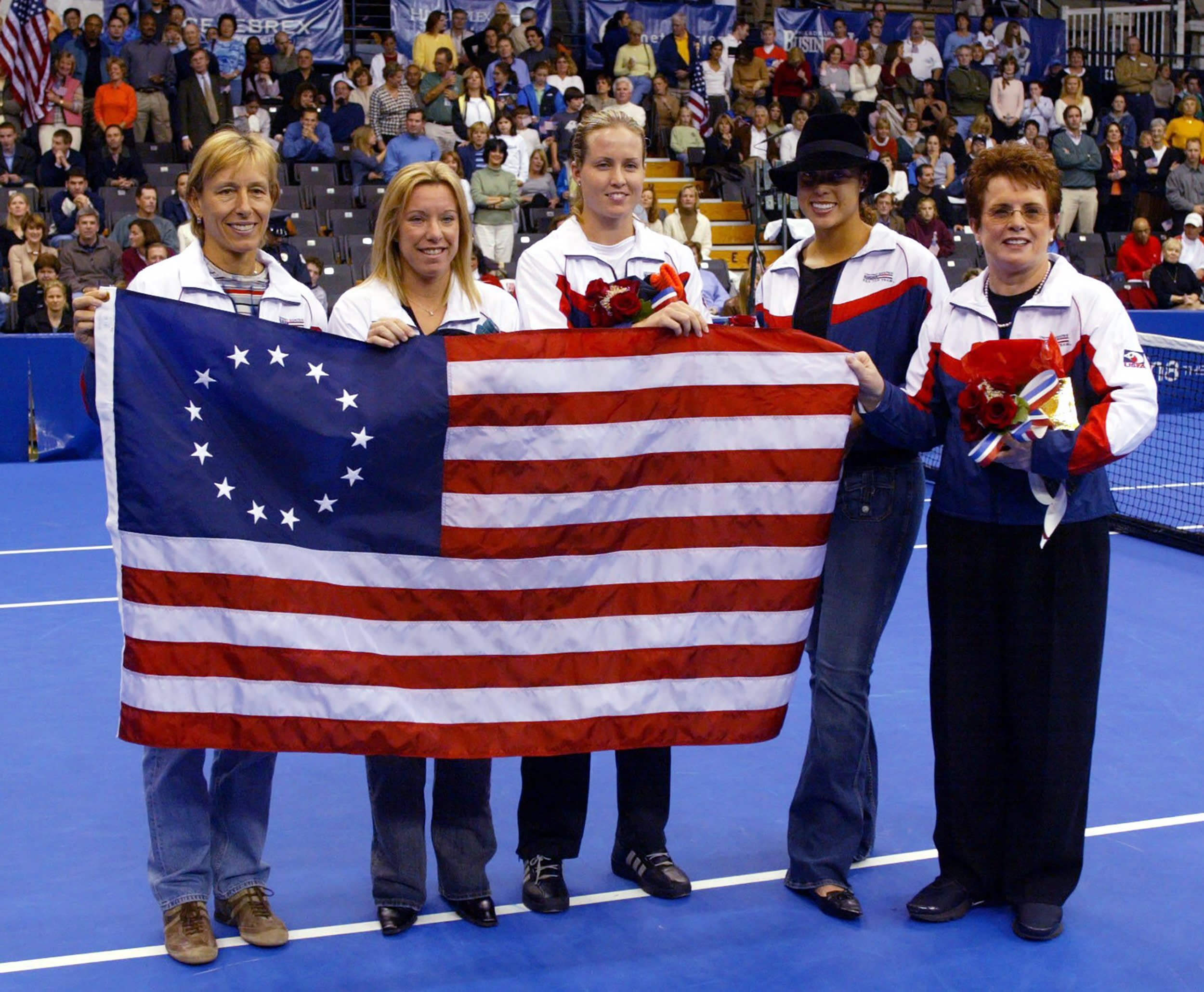FILE - In this file photo dated Thursday, Oct. 30, 2003, U.S. Fed Cup members from left, Martina Navrartilova, Lisa Raymond, Meghann Shaughnessy, Alexandra Stevenson and Fed Cup Captain Billie Jean King, accept a replica of the Betsy Ross Flag at the Advanta Championships, in VIllanova, USA. The Fed Cup is changing its name to honour tennis great Billie Jean King, becoming The Billie Jean King Cup, the first major global team competition to be named after a woman, it is announced Thursday Sept. 17, 2020.(AP Photo/Miles Kennedy, FILE)