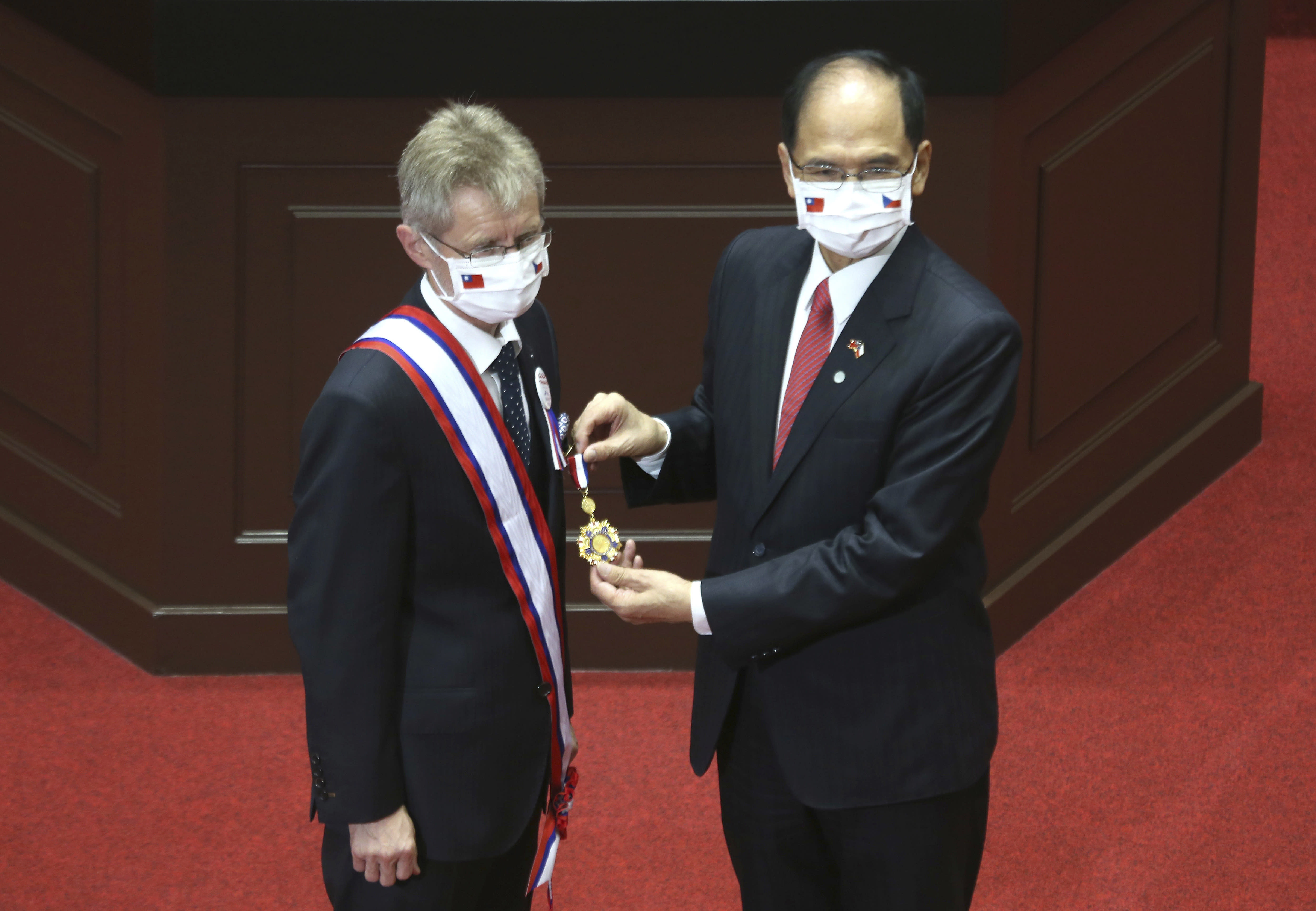 The Czech Senate President Milos Vystrcil, left, is decorated with a medal by President of the Legislative Yuan Yu Shyi-kun before Vystrcil delivers a speech at Legislative Yuan in Taipei, Taiwan, Tuesday, Sept. 1. 2020. Vystrcil arrived in Taiwan on Sunday accompanied by Prague Mayor Zdenek Hrib and more than 80 representatives from government, business and academia on a 6-day visit. (AP Photo/Chiang Ying-ying)