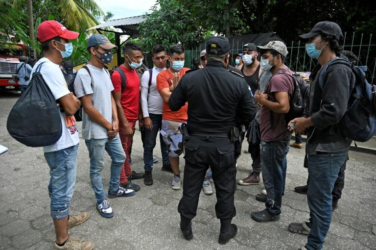 A policeman speaks with Honduran migrants, part of a US-bound caravan, outside a migrant shelter in the municipality of San Marcos, Guatemala, on October 3, 2020
