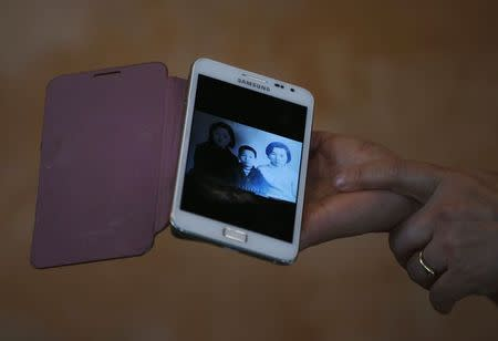 Kim Young-ja, a sister of South Korean abductee Kim Young-nam who is living in North Korea, shows her mobile phone displaying an old picture taken when she was 10 with her abducted brother (C, in picture), during an interview with Reuters in Jeonju July 2, 2014. REUTERS/Kim Hong-Ji