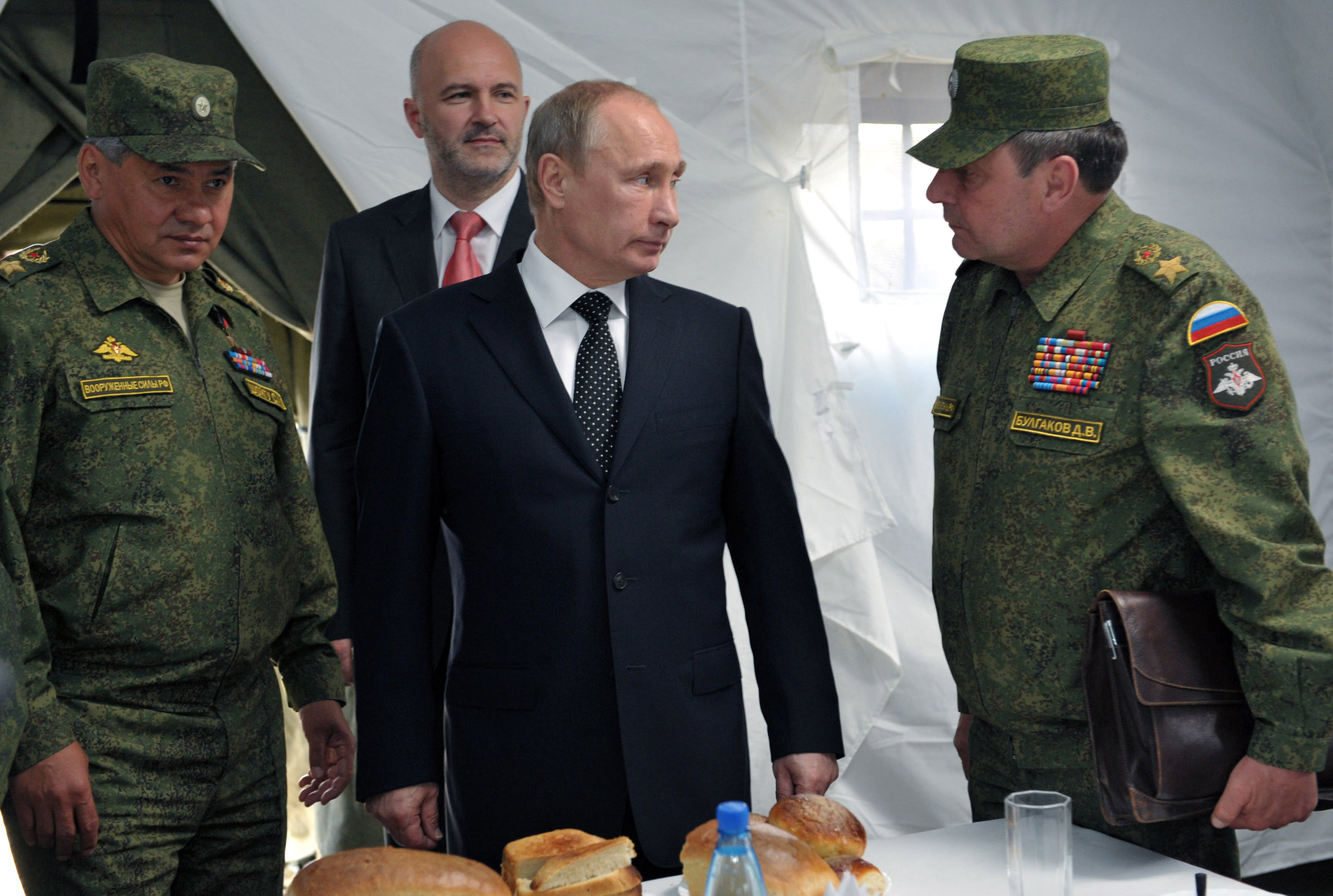 Russian President Vladimir Putin, center, listens to Deputy Defense Minister Dmitry Bulgakov, right, as Defense Minister Sergei Shoigu, left, and Gov. of Baikal region Konstantin Ilkovsky, background, observe military exercises near the Baikal Lake on Wednesday, July 17, 2013. Russia has launched its biggest military maneuvers since Soviet times, involving 160,000 troops and about 5,000 tanks across Siberia and the far eastern region. (AP Photo/RIA Novosti, Alexei Nikolsky, Presidential Press Service, Pool)