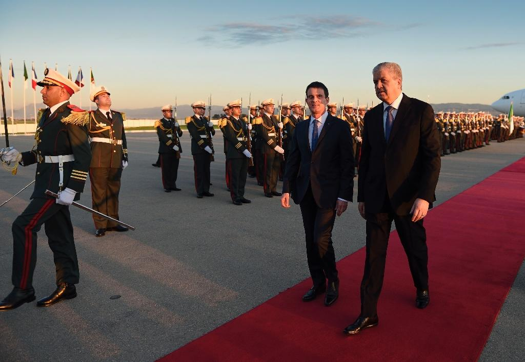Algeria's Prime Minister Abdelmalek Sellal (R) welcomes his French counterpart Manuel Valls upon his arrival at Algiers airport on April 9, 2016