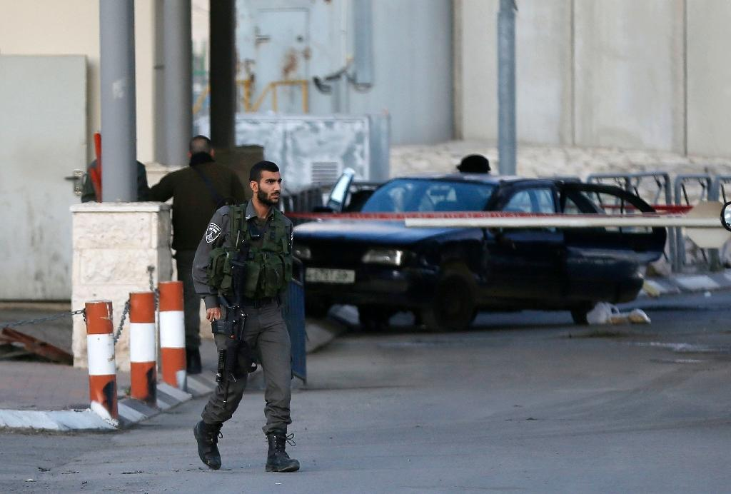 Israeli security forces gather around the car of a Palestinian driver who attempted to ram his vehicle into Israeli police and soldiers at the Qalandia checkpoint in the occupied West Bank on December 18, 2015 (AFP Photo/Ahmad Gharabli)