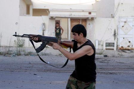 Fighter from Libyan forces allied with the U.N.-backed government aims his weapon during a battle with Islamic State fighters in Sirte