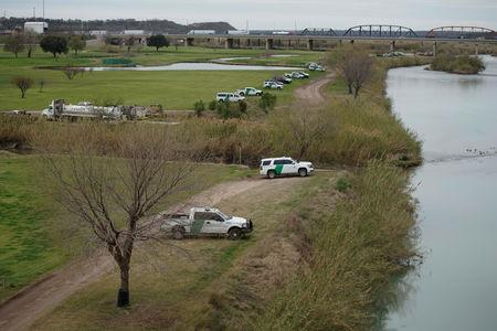 U.S. border patrol vehicles, seen through the fence of the bridge (not pictured) connecting Eagle Pass, Texas, with Piedras Negras, Mexico, are stationed near the banks of Rio Bravo as seen from Piedras Negras, February 8, 2019. REUTERS/Alexandre Meneghini