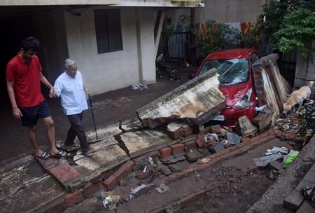 Residents walk past a damaged car after a wall collapsed following heavy rains in Pune