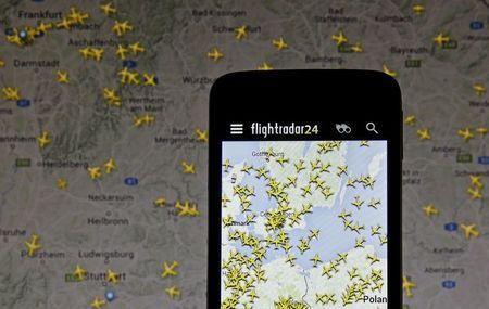 The Flightradar24 application is pictured on a smartphone in front of a computer screen displaying the website in this illustration taken in Zenica, Bosnia and Herzegovina May 18, 2015. REUTERS/ Dado Ruvic